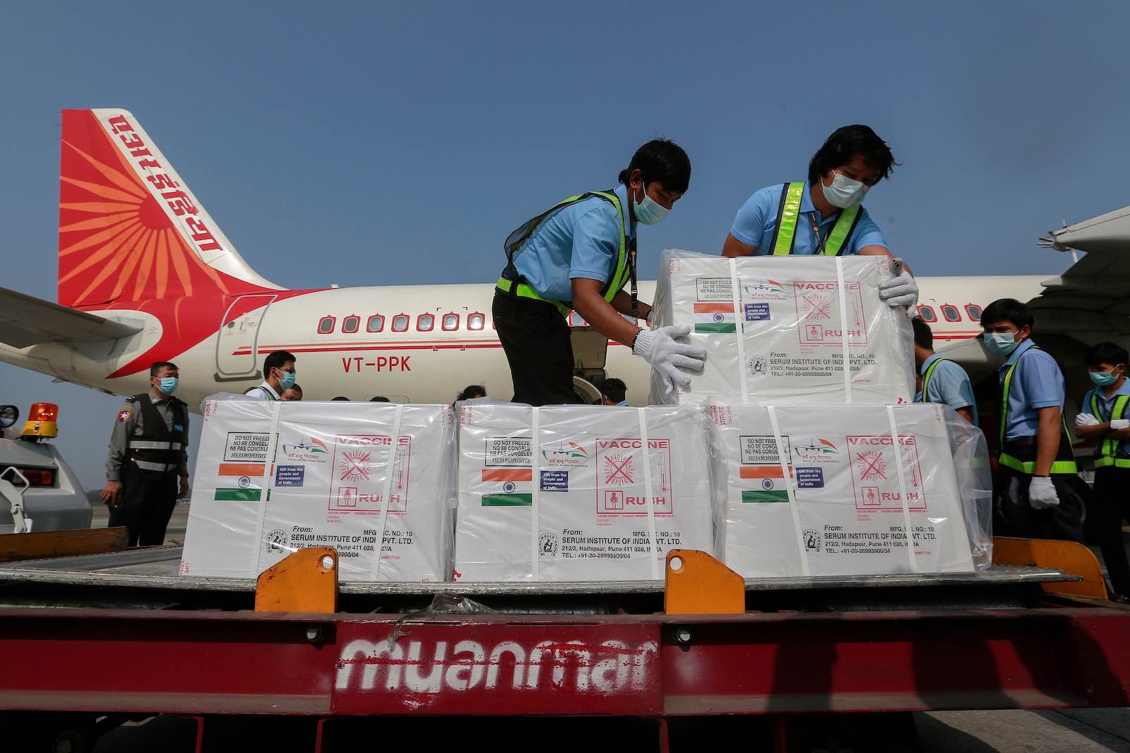 Workers in Myanmar unload a shipment of Covid-19 vaccine manufactured in India (STR/AFP via Getty Images)