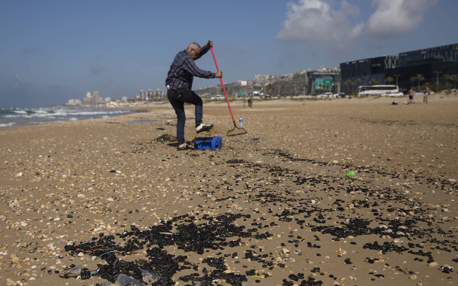 Cleaning tar from a beach in Haifa, Israel, following a suspicious oil spill in the Mediterranean, 25 February (Amir Levy/Getty Images)