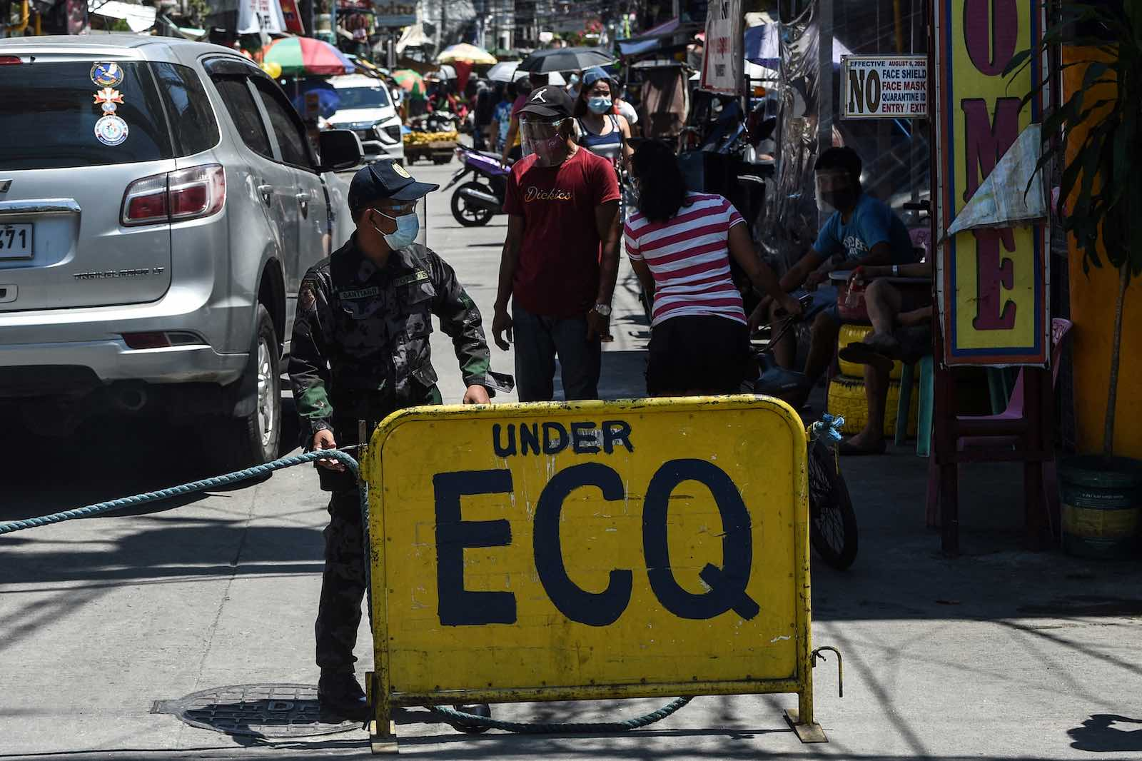 A policeman guards the entrance to a Manila neighbourhood under strict quarantine, 16 March (Ted Aljibe/AFP via Getty Images)