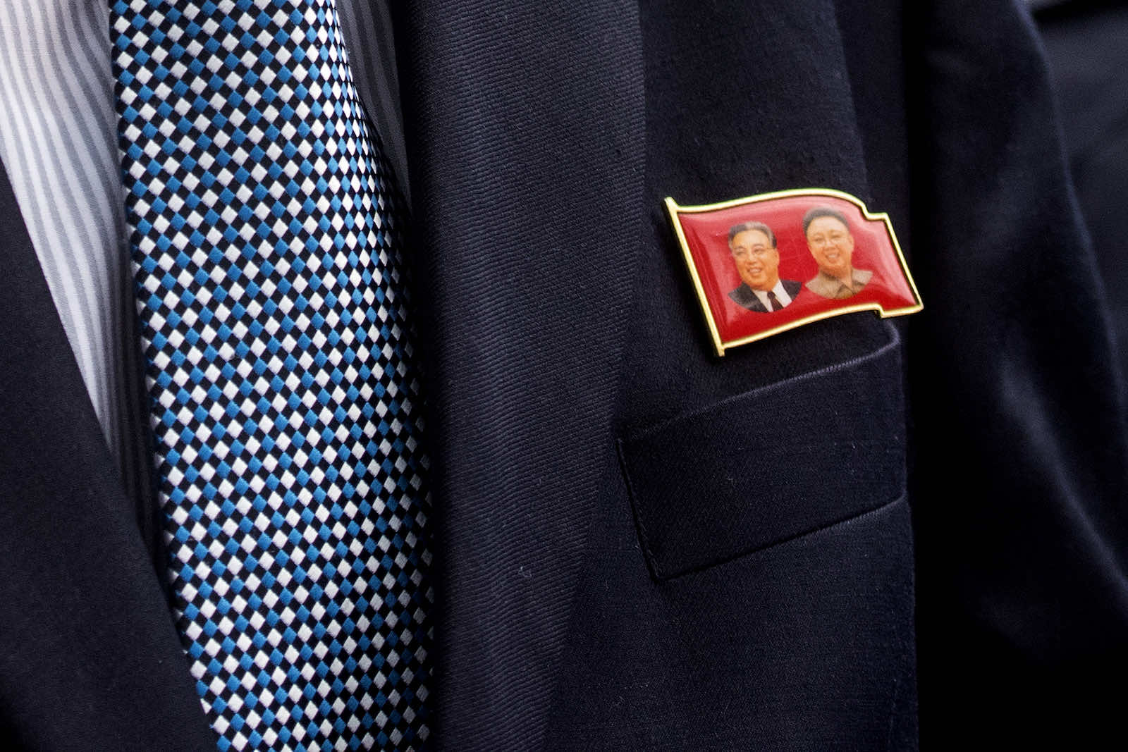 A North Korean diplomat wears a badge depicting former leaders Kim Il Sung and Kim Jong Il (Vivian Lo via Getty Images)
