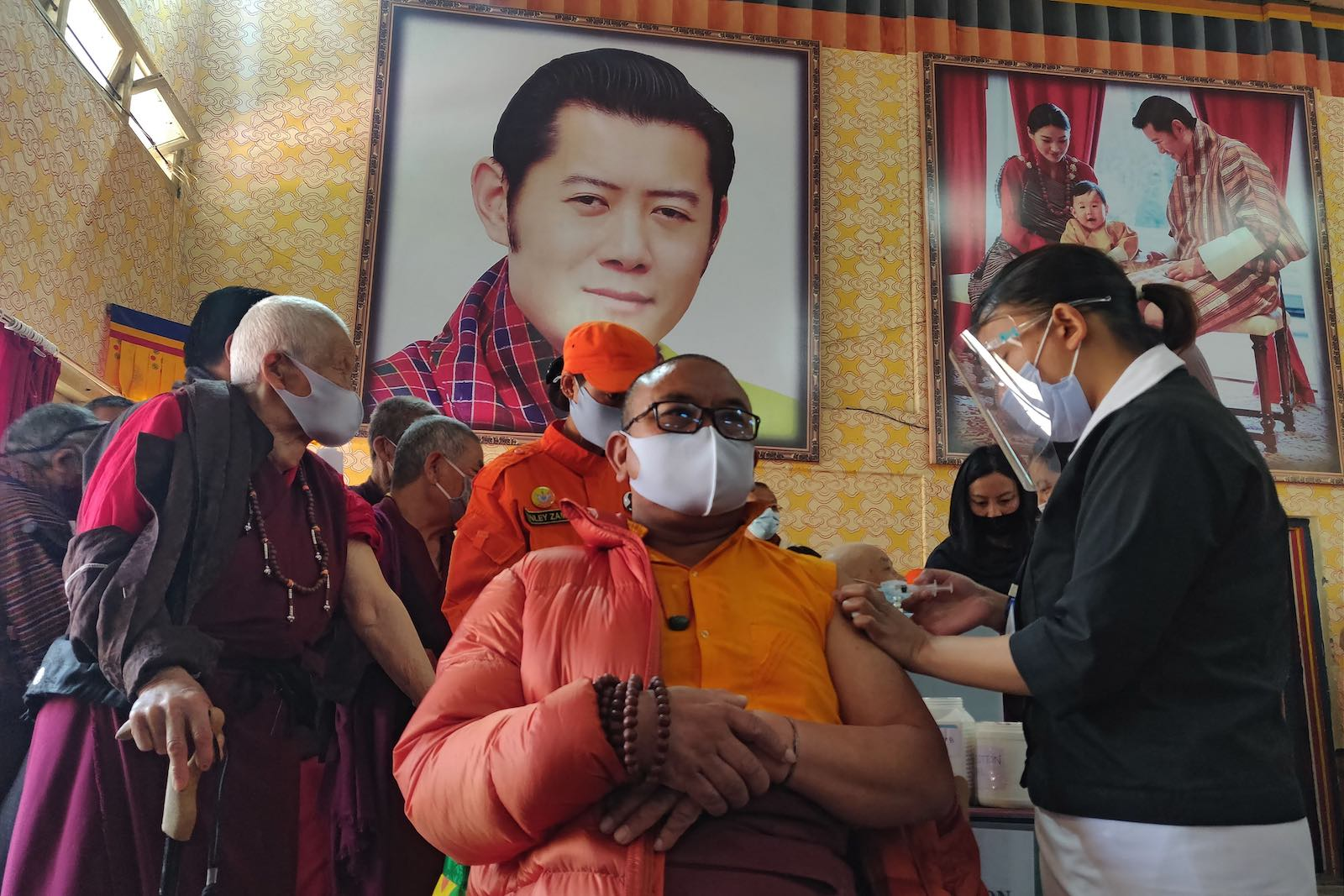 A Buddhist monk is vaccinated last month sitting in front of a portrait of Bhutan's King Jigme Khesar Namgyel Wangchuck (Upasana Dahal/AFP via Getty Images)