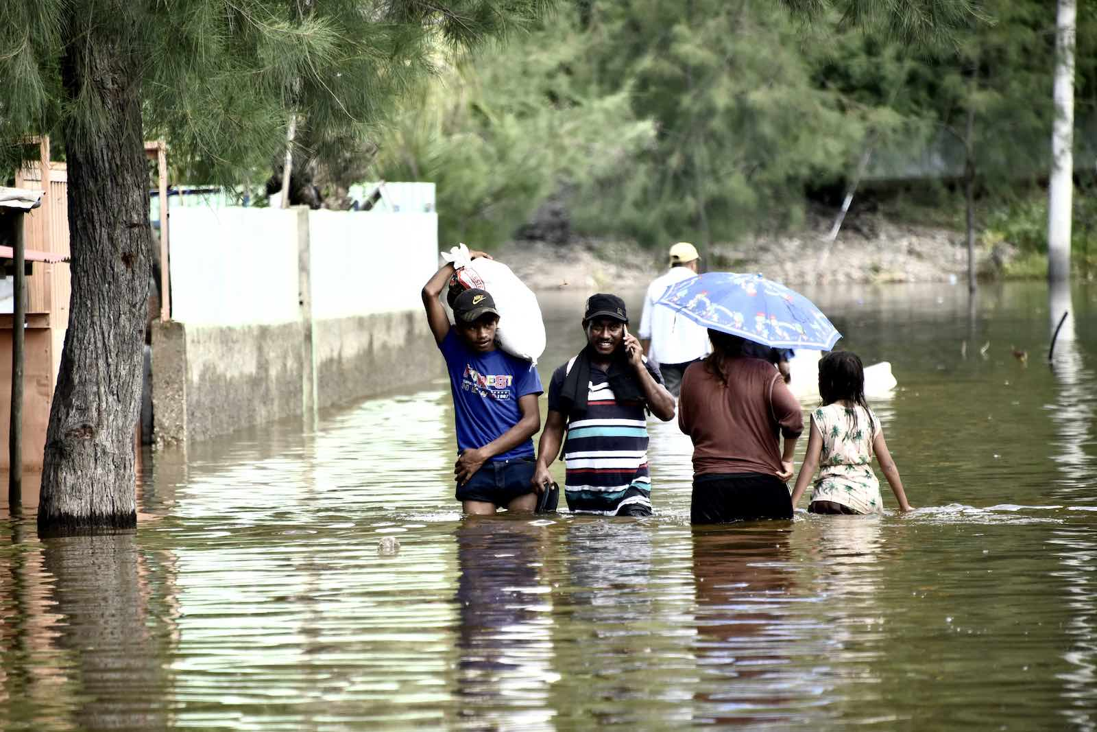 Dili residents wade through a flooded street on 9 April 2021 (Valentino Dariel Sousa/AFP via Getty Images)