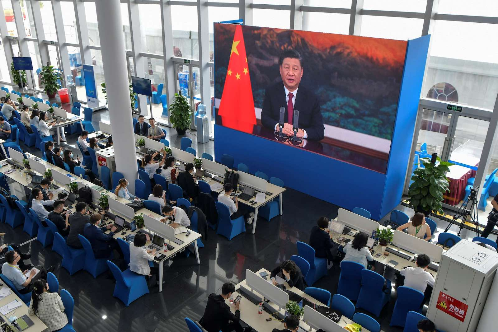 Journalists watch on screen as China's President Xi Jinping delivers a speech during the opening of the Boao Forum for Asia on 20 April (STR/AFP via Getty Images)