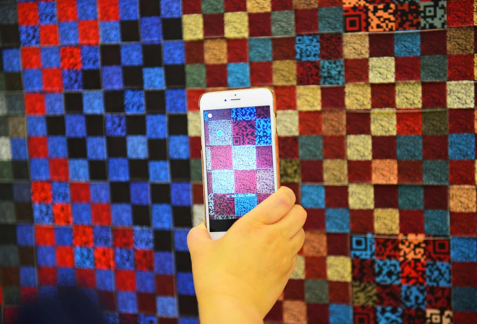 A visitor scans the QR code on an exhibit at an exhibition of traditional crafts in Urumqi, Xinjiang (Hou Zhaokang/Xinhua via Getty Images)
