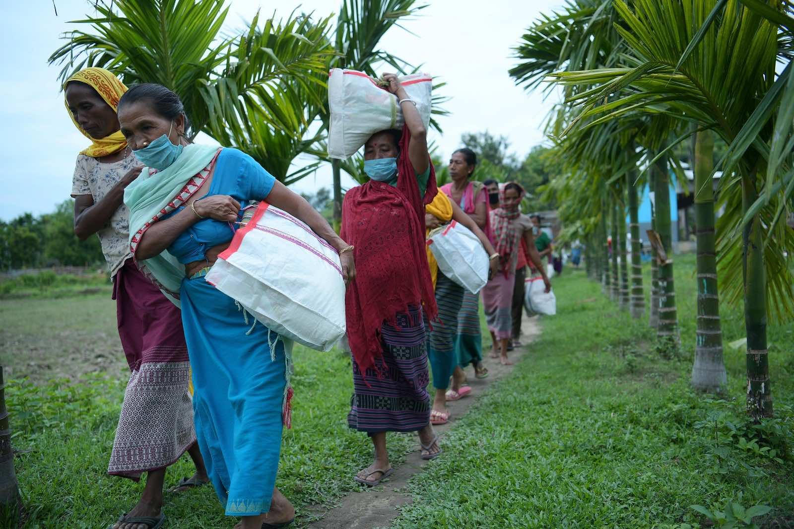 Residents carry food distributed by an NGO after the government eased Covid-19 restrictions in Jampuijala, India, 16 June 2021 (Str/Xinhua via Getty Images)