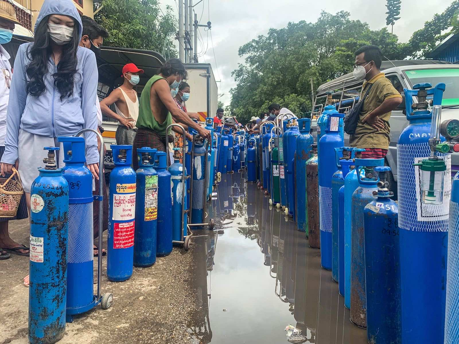 People stand with empty oxygen canisters as they wait to fill them up outside a factory in Yangon on 11 July (Ye Aung Thu/AFP via Getty Images)