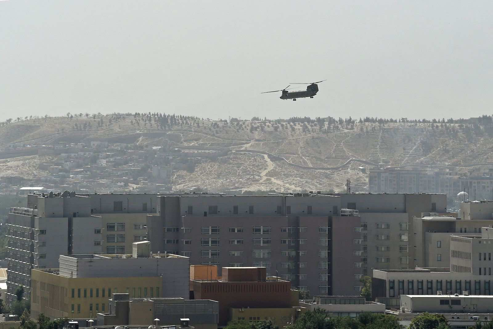 A US military helicopter is pictured flying above the US embassy in Kabul on 15 August (Wakil Kohsar/AFP via Getty Images)