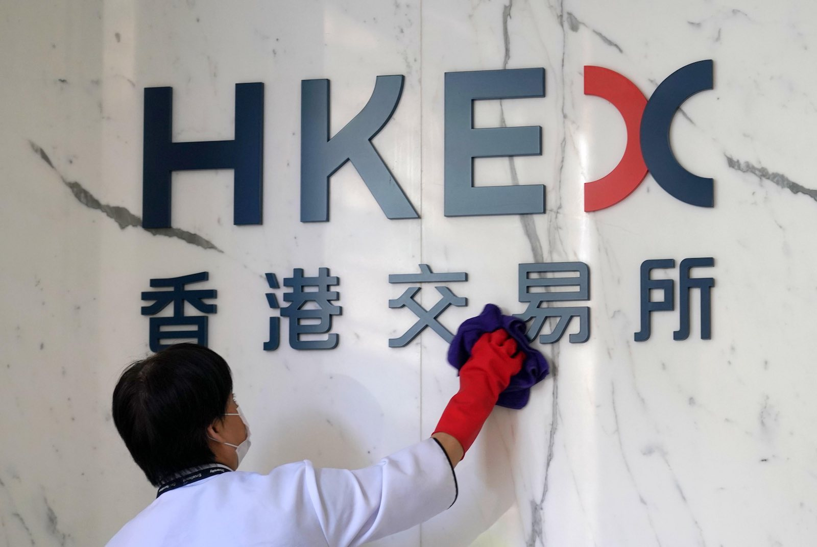A worker cleans the logo of Hong Kong Exchanges and Clearing (HKEX), June 2020 (Zhang Wei/China News Service via Getty Images)