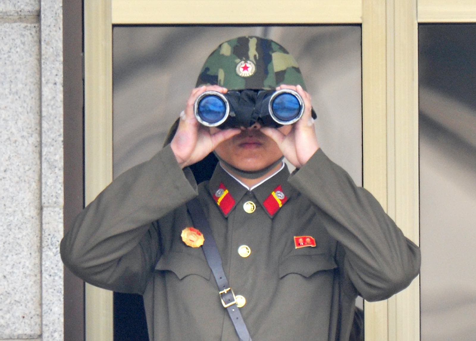 A North Korean soldier watches from his quarters at the truce village of Panmunjom in the demilitarised zone, April 2013 (Kim Jae-Hwan/AFP via Getty Images)