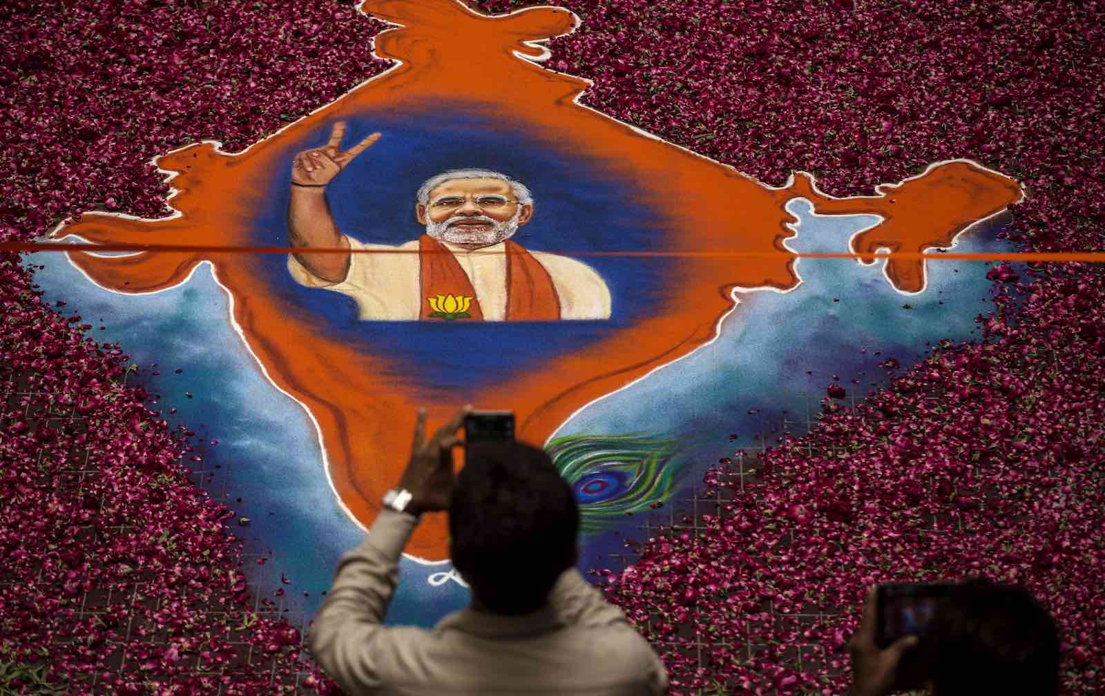 A supporter takes a picture of a map of India made of flowers with a picture of BJP leader Narendra Modi in Ahmedabad, India during the 2014 elections (Photo: Kevin Frayer/Getty)