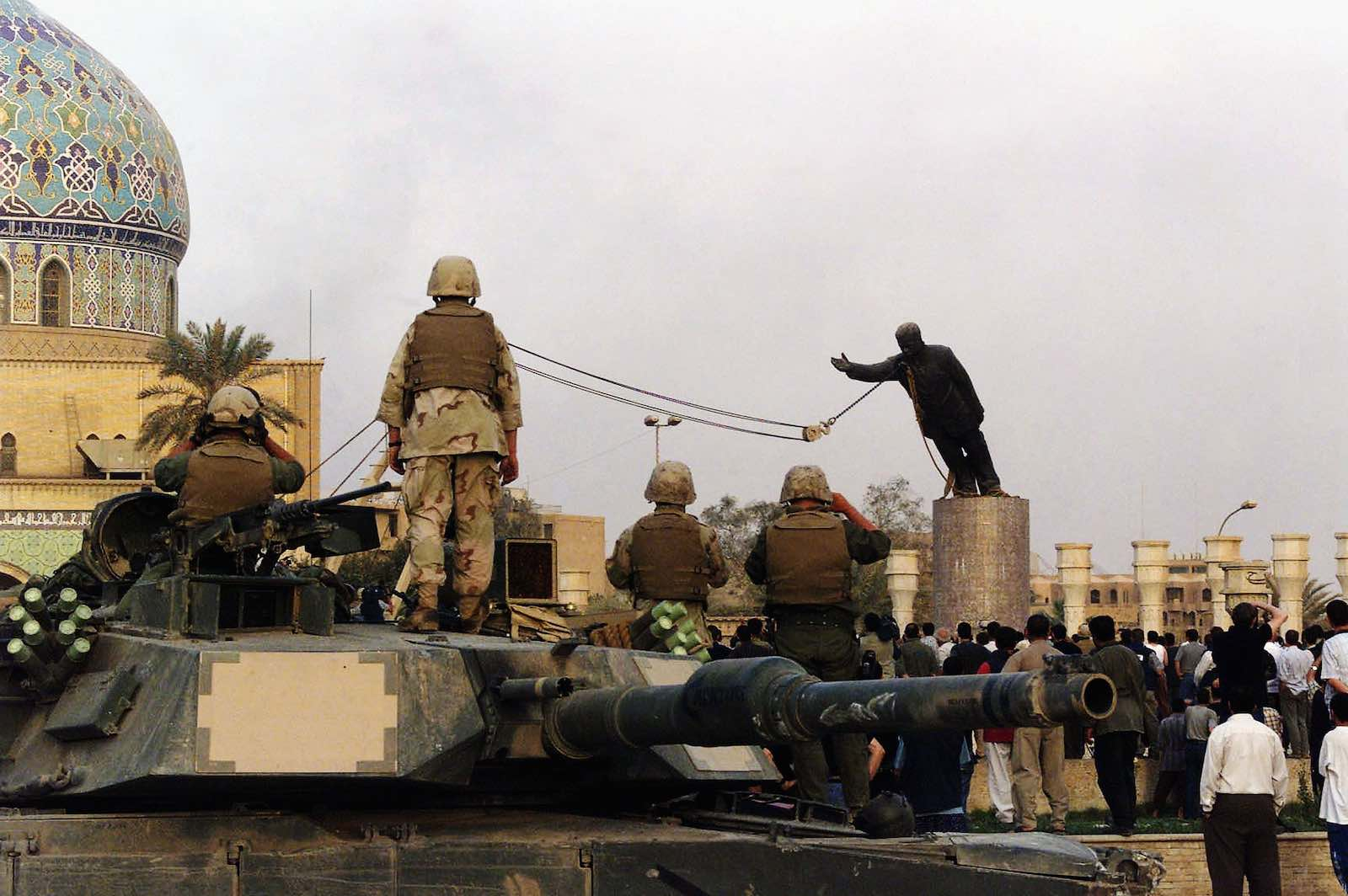 US marines and Iraqis watch the toppling of Saddam Hussein's statue in al-Fardous square in Baghdad, 9 April 2003 (Wathiq Khuzaie /Getty Images)