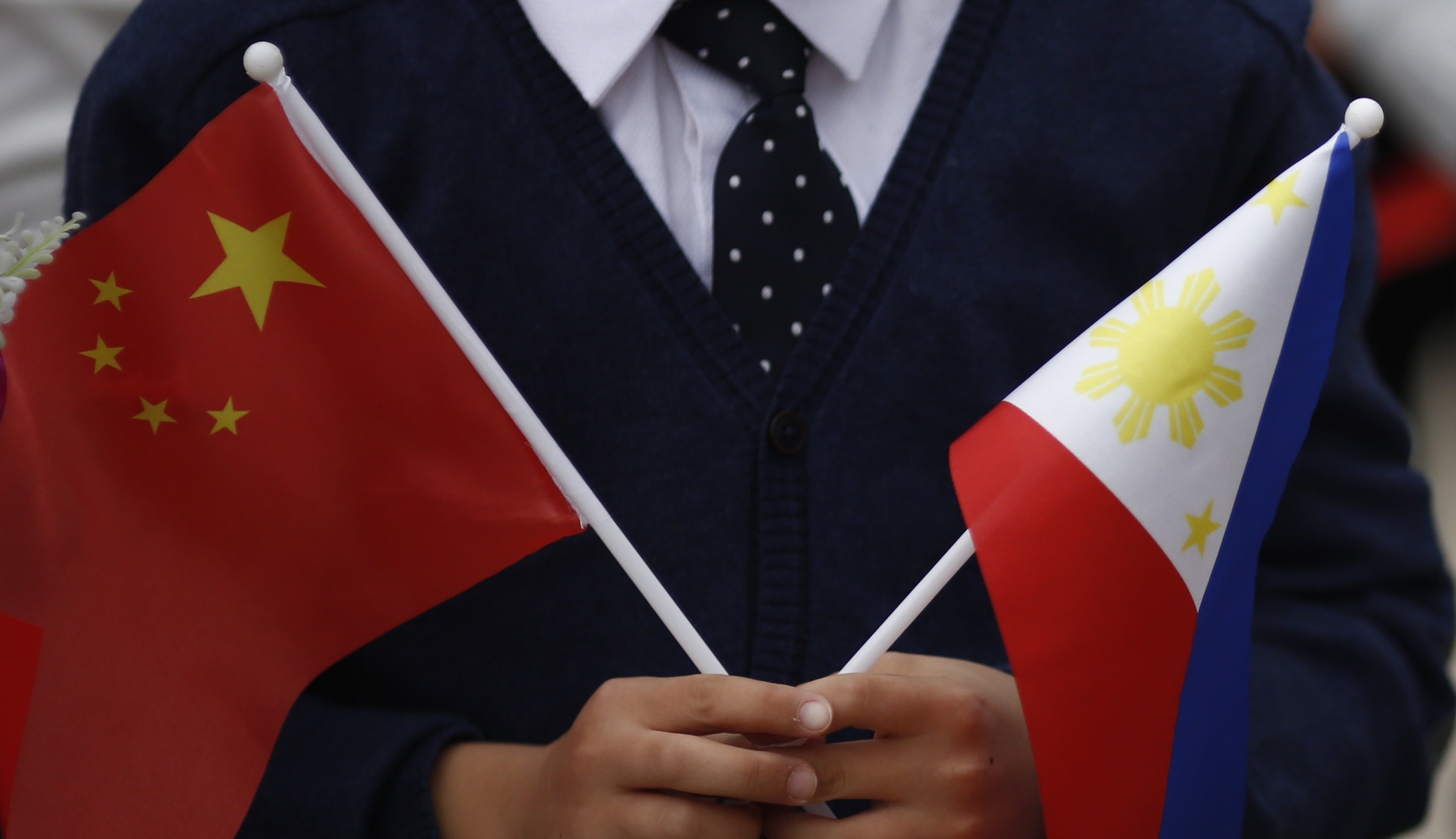 Children hold national flags during Philippine President Rodrigo Duterte's visit to Beijing in 2016 (Photo: Thomas Peter-Pool/Getty)