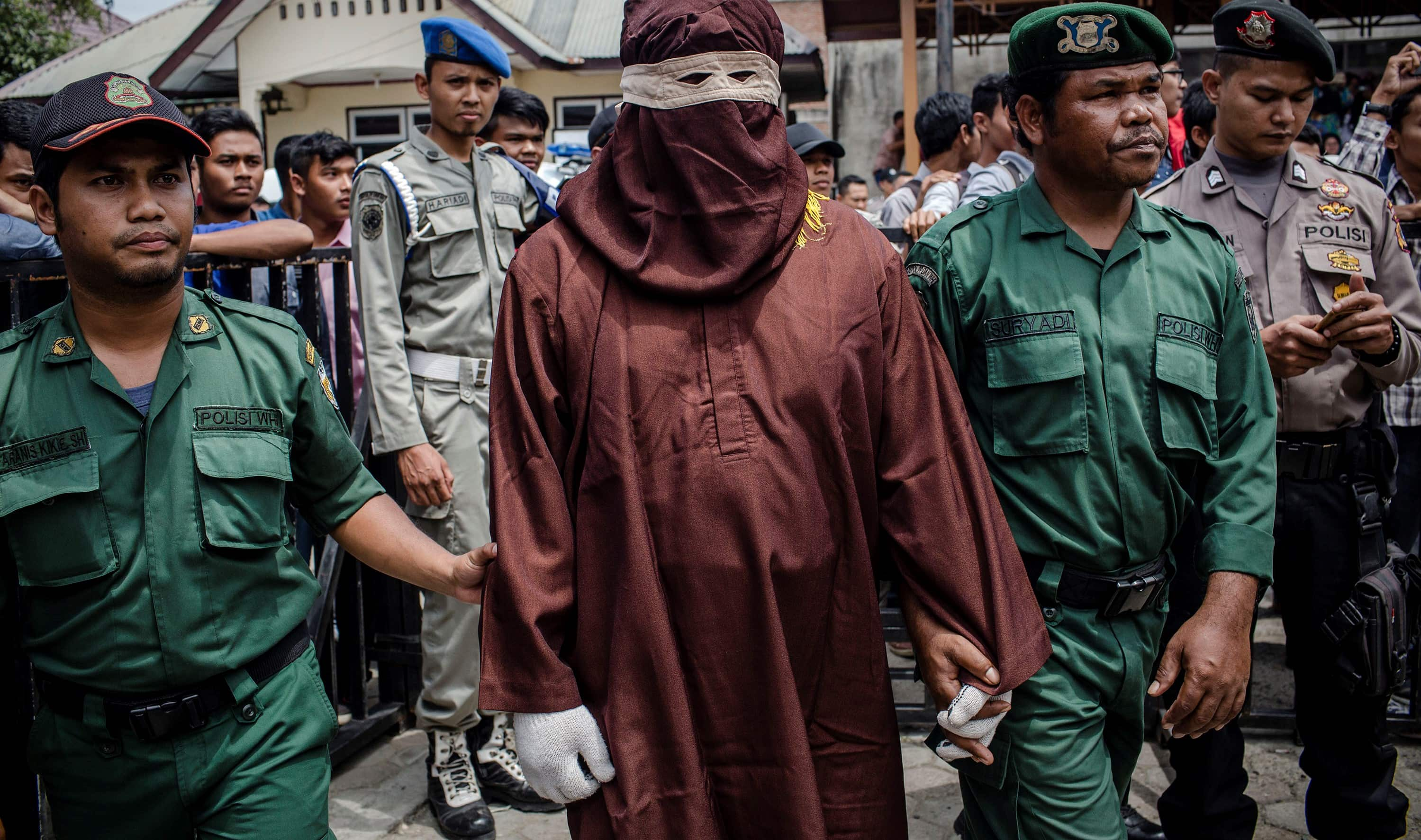 A judicial executor known as an 'algojo' stands by before a public caning in Aceh, Indonesia, March 2017 (Photo: Ulet Ifansasti/Getty Images)