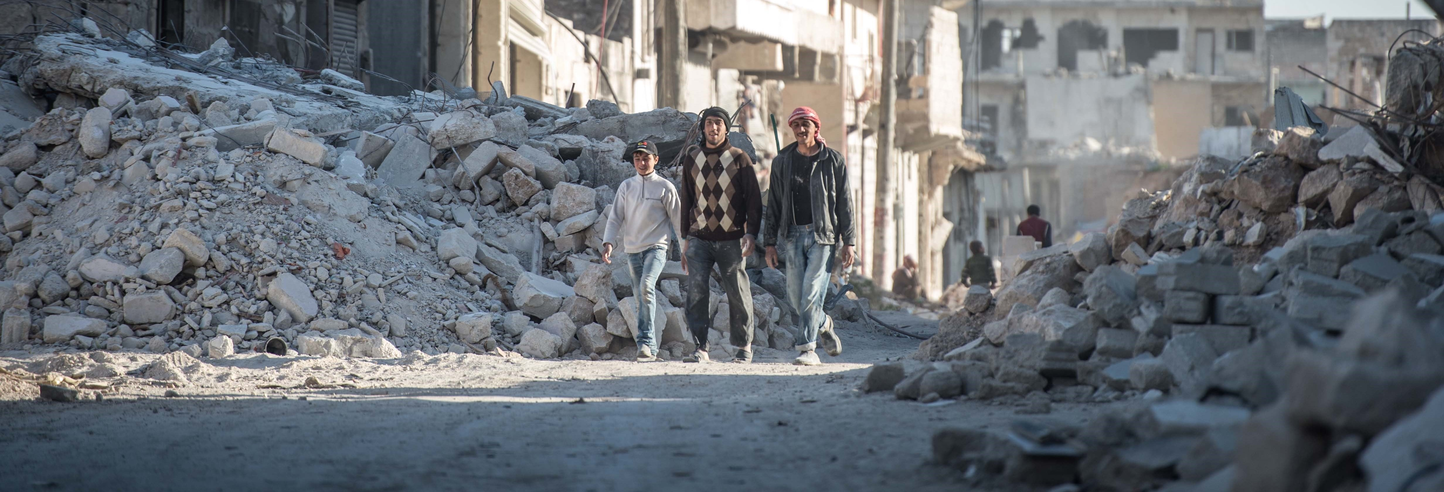 Syrians walk past damaged houses in Al-Bab district of Aleppo, Syria (Photo: Kerem Kocalar/Anadolu Agency/Getty Images)