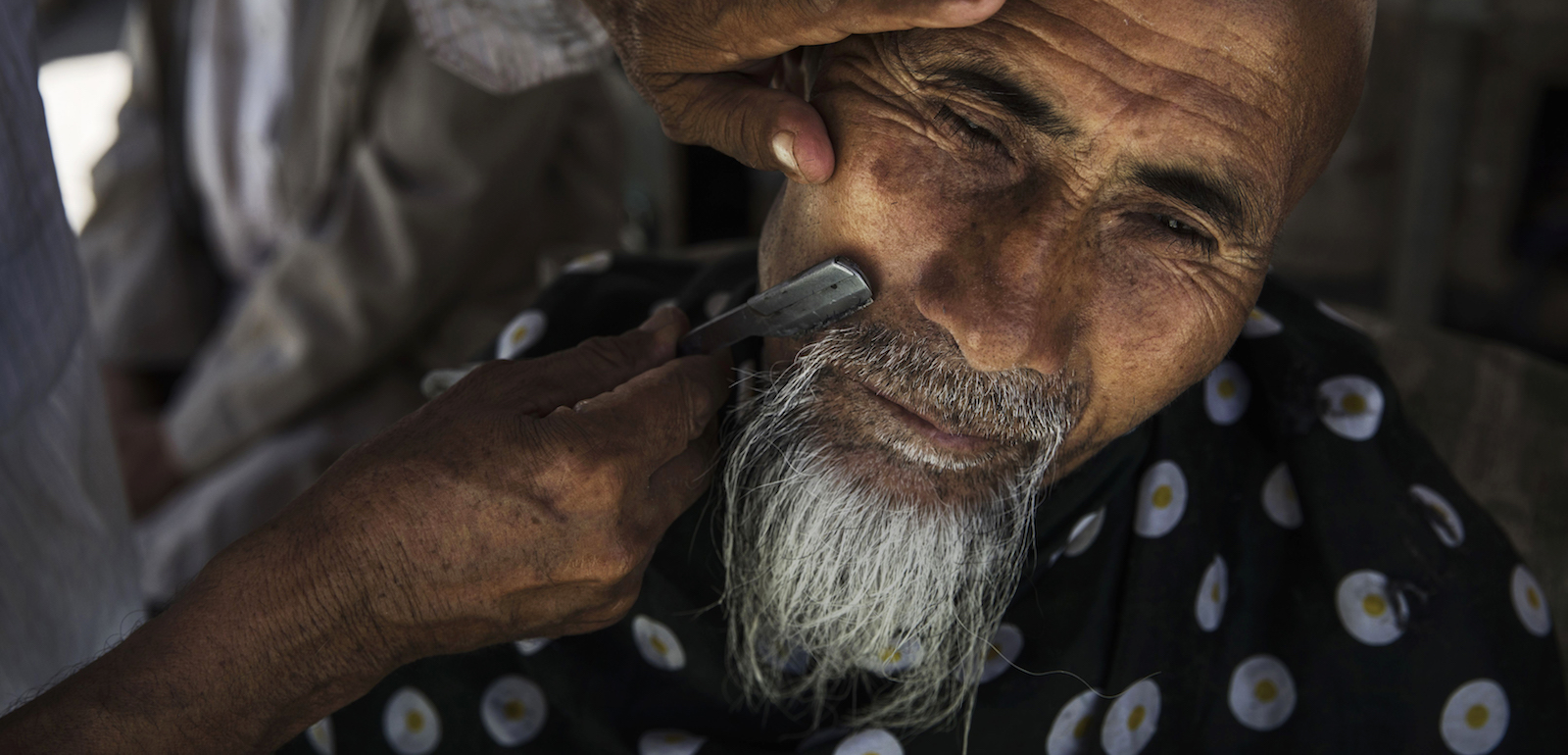 "An ethnic Uighur man has his beard trimmed: religious observances such as having an ""irregular beard"" have become seen as ""expressions of extremification"" (Phtoto: Kevin Frayer via Getty)"