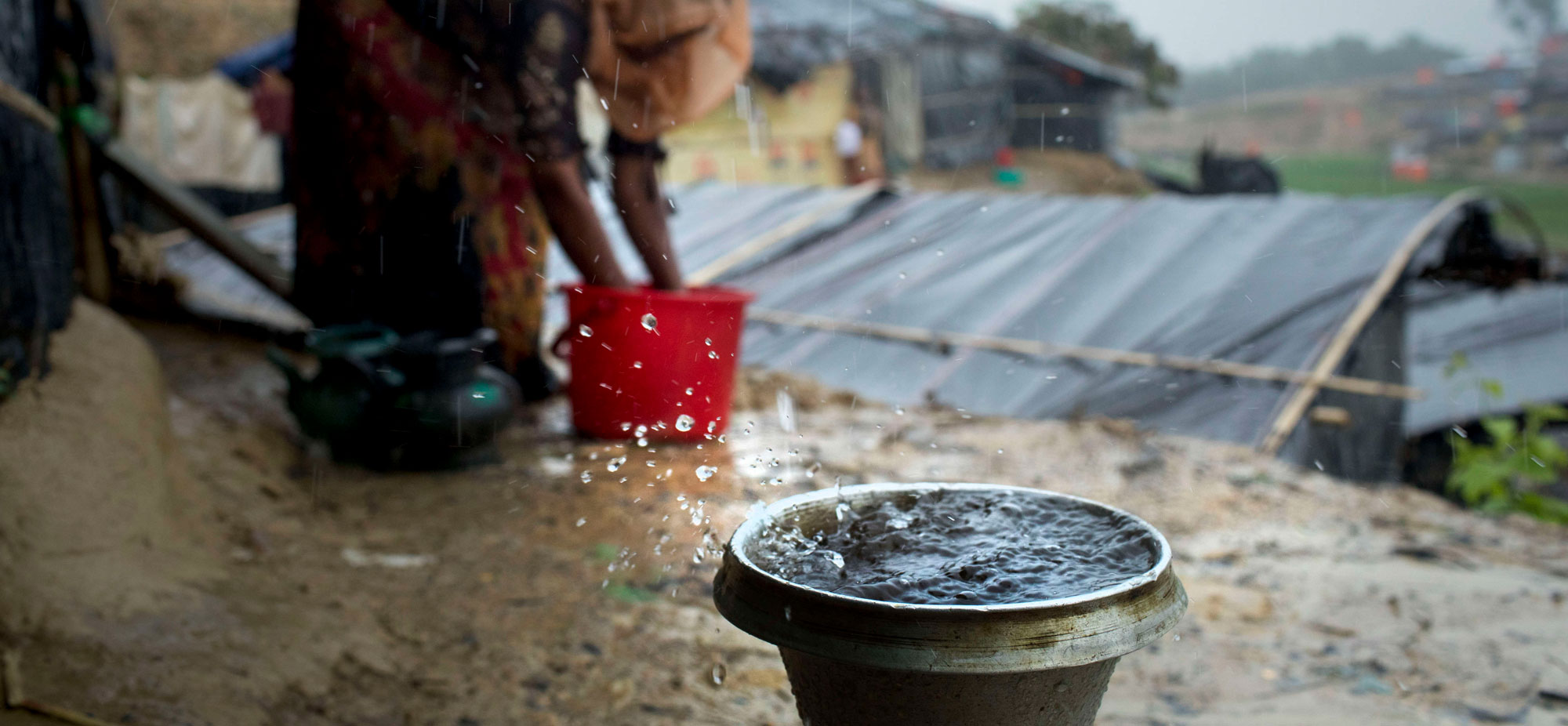 A Rohingya refugee collects drinking water in heavy rain at Ukhiya, Cox's Bazar (Photo by K M Asad/Getty)