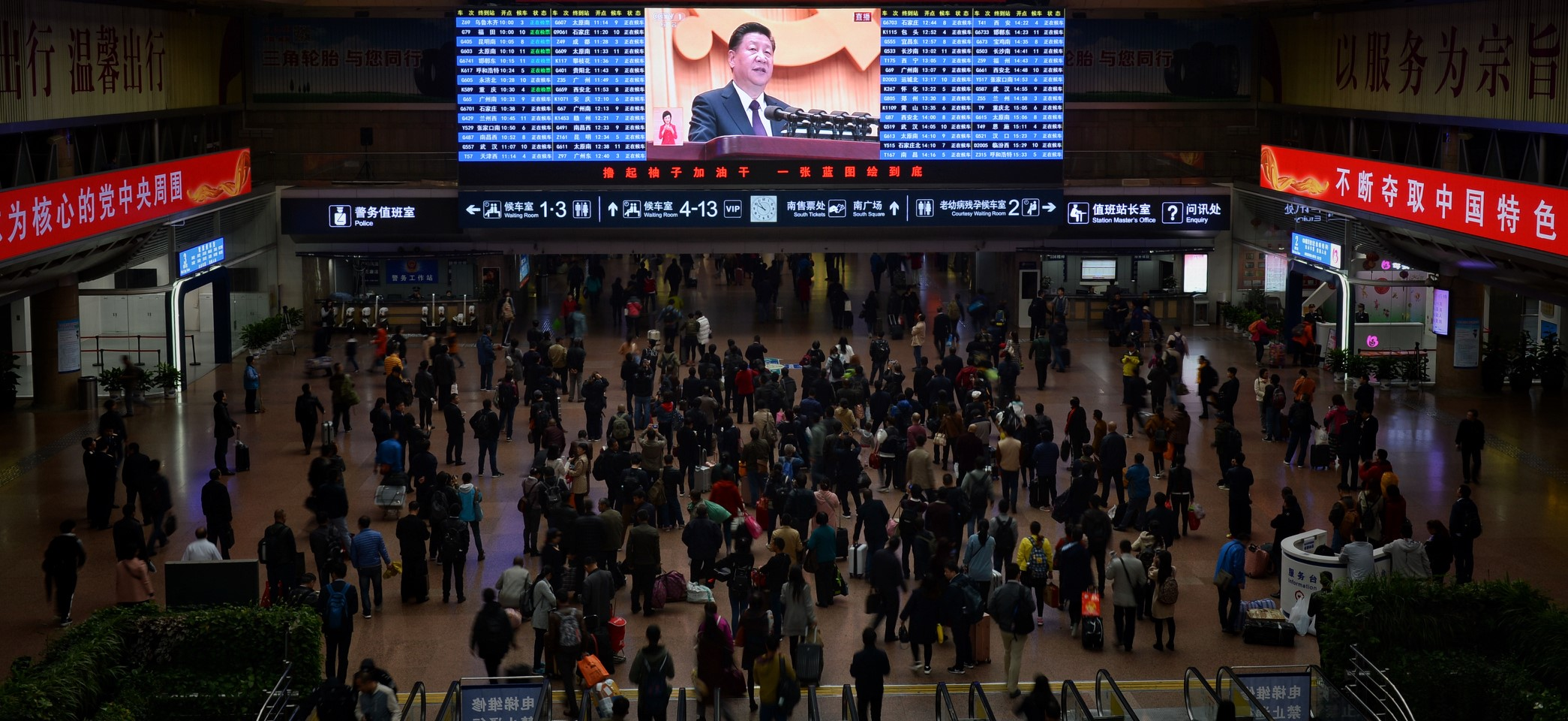 Passengers watch a broadcast of the opening ceremony for the 19th Party Congress at a Beijing railway station, October 2017 (Photo: VCG/Getty Images)