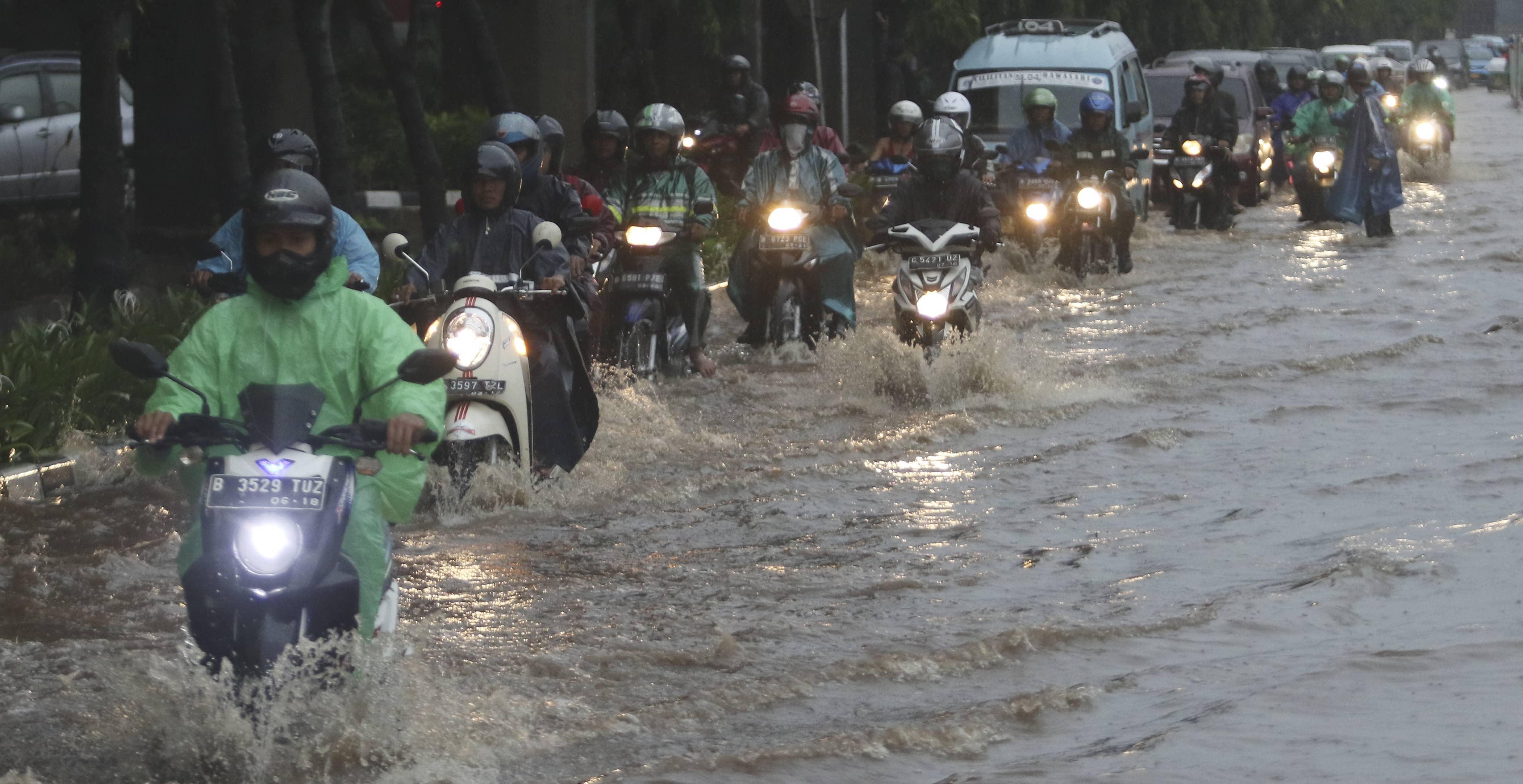 Motorcyclists pass floodwaters in easter Jakarta in December (Photo: Eko Siswono Toyudho/Getty)
