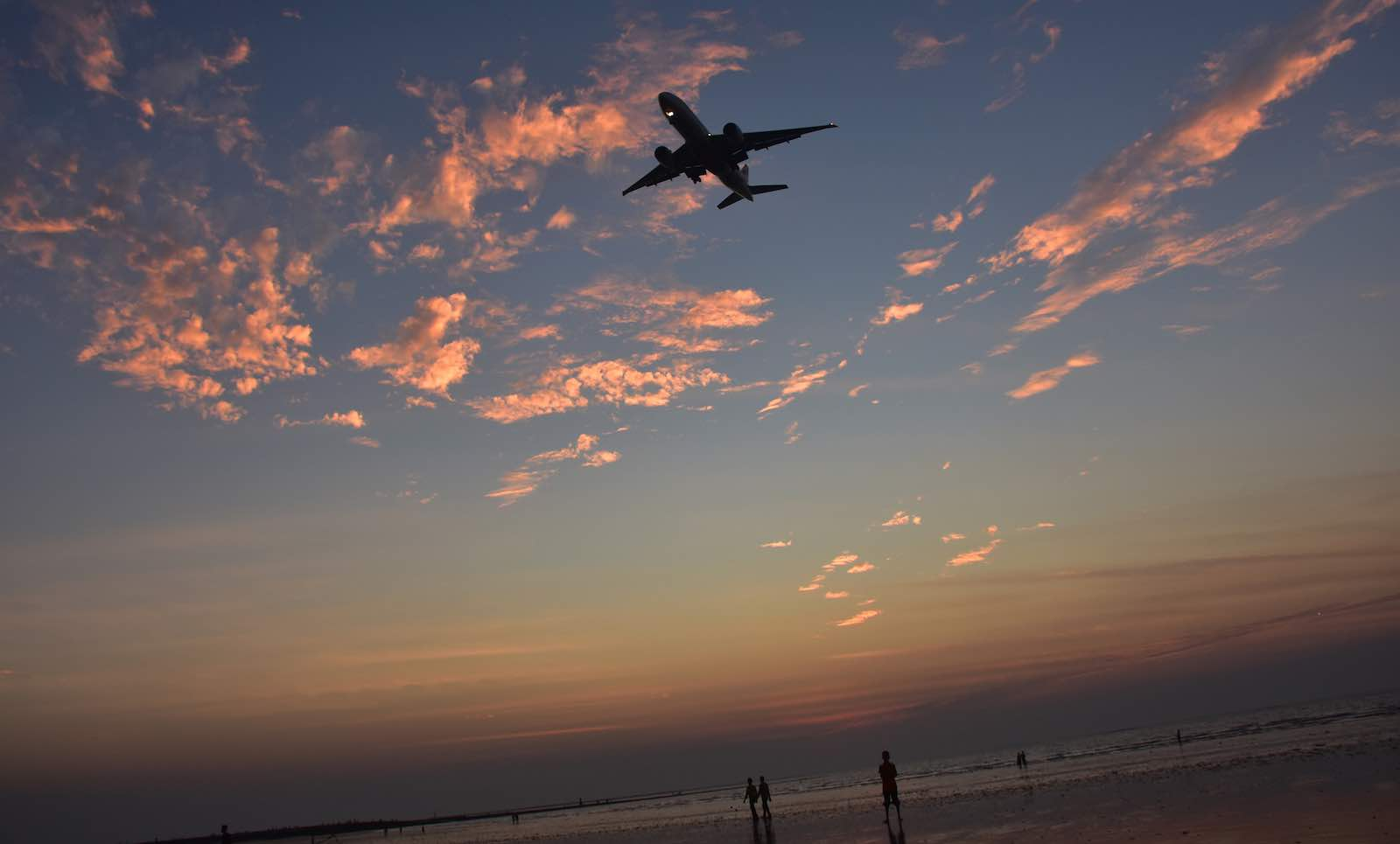 A plane flying over Juhu Beach in Mumbai, India (Photo: Azhar Khan via Getty)