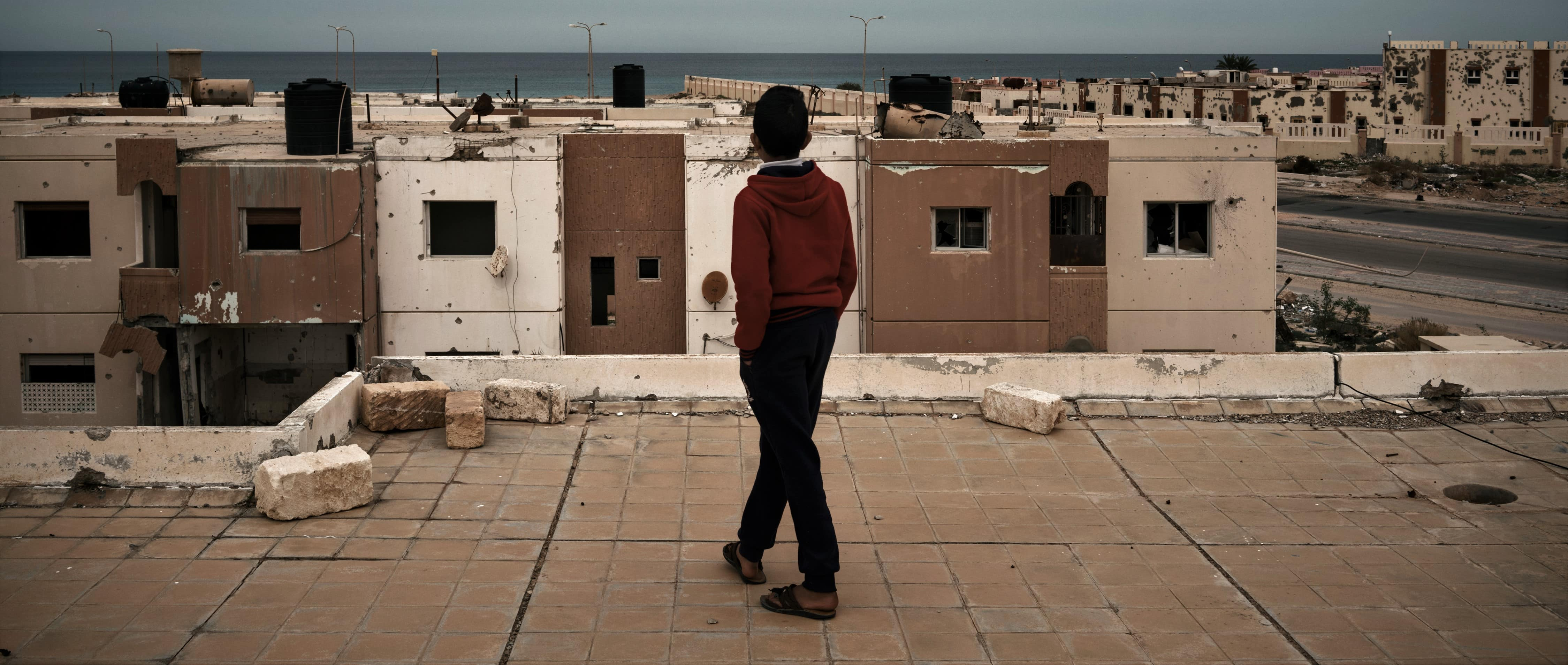 A boy walks along a building's roof in Sirte, Libya, December 2017 (Photo: Washington Post/Getty Images)