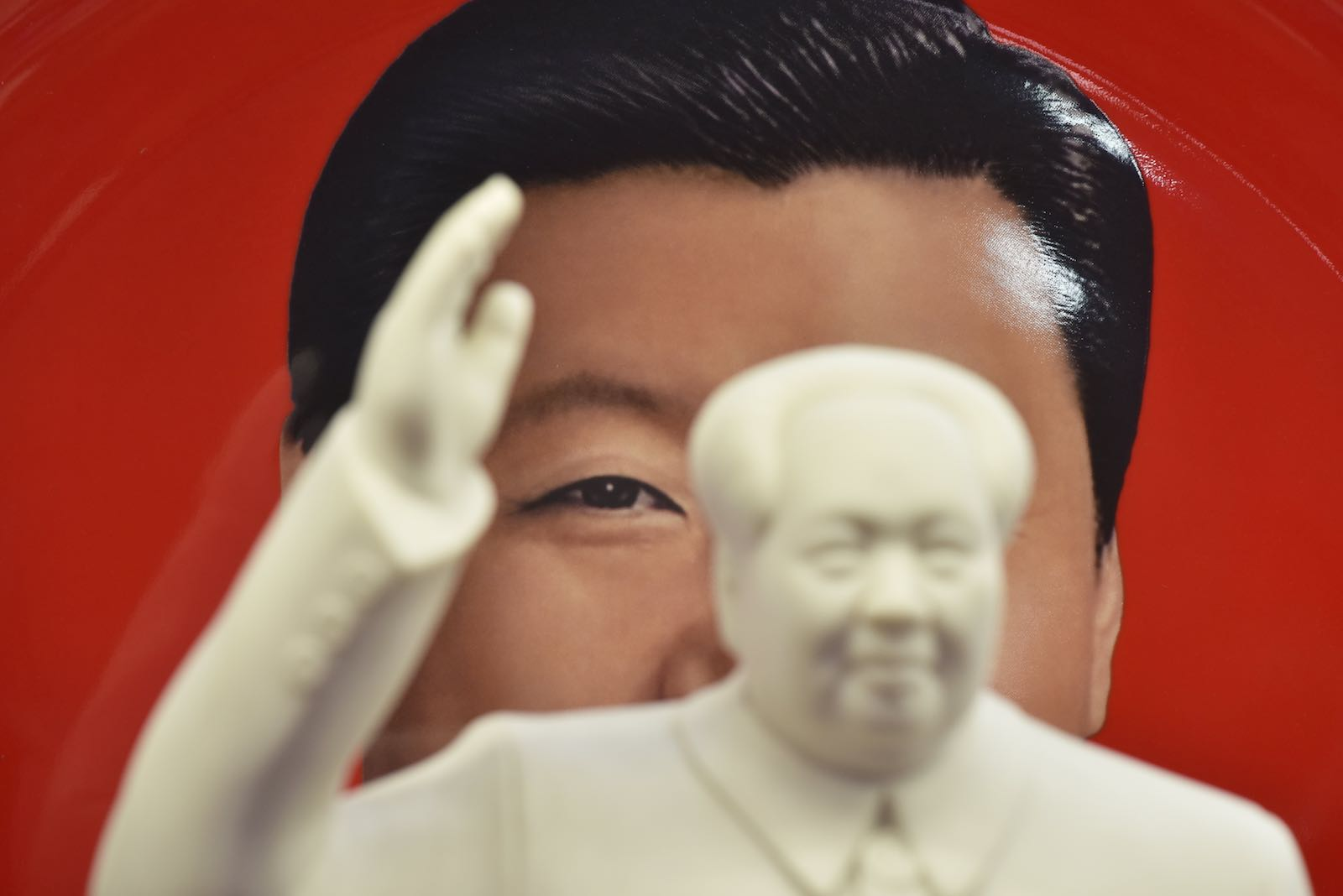 A decorative plate featuring an image of China's President Xi Jinping is seen behind a statue of late communist leader Mao Zedong at a souvenir store next to Tiananmen Square in Beijing (Greg Baker/AFP/Getty Images)