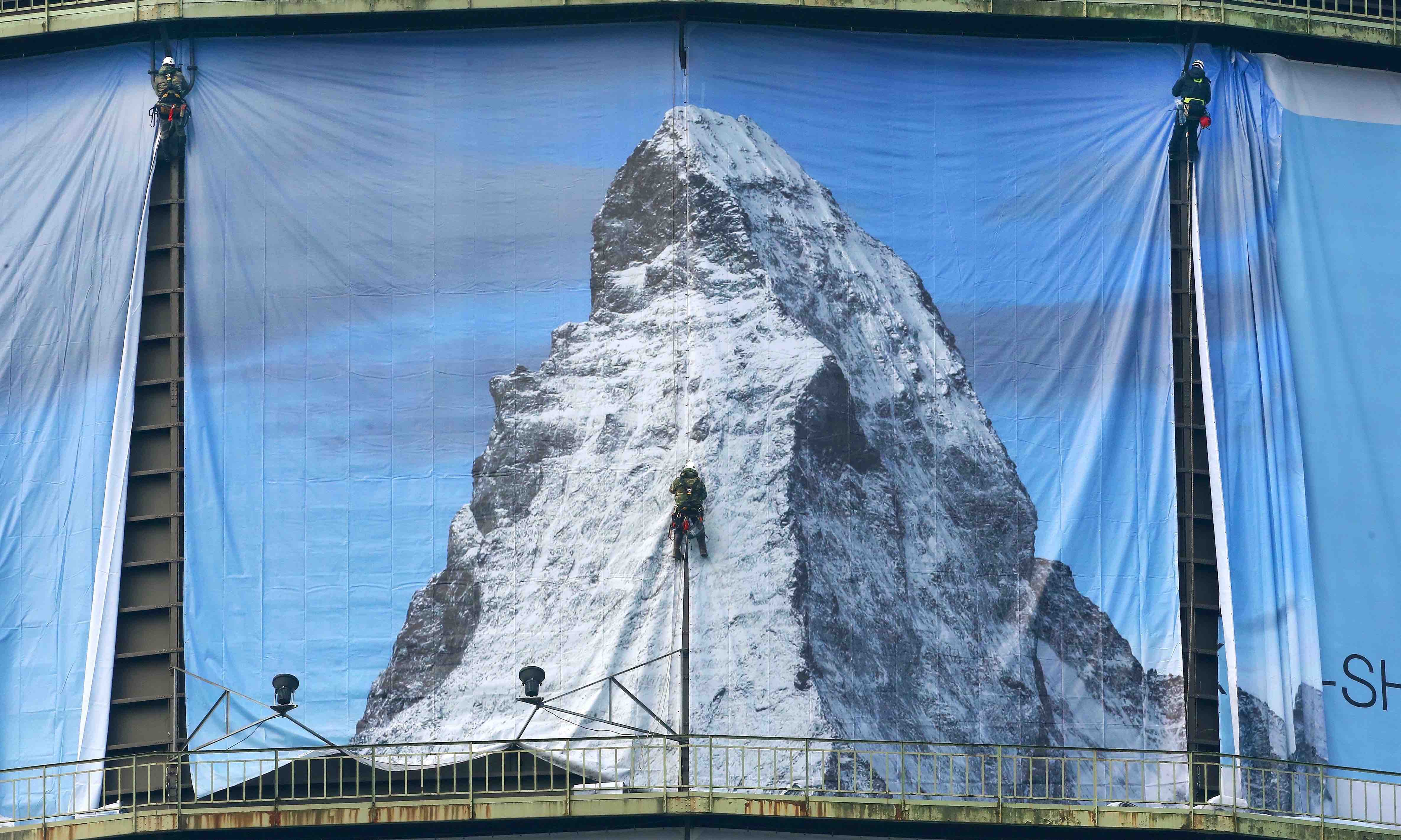 "Workers hang a 1400 square-metre banner to promote the exhibition ""The Call of the Mountains"" on 2 March (Roland Weihrauch/Getty)"