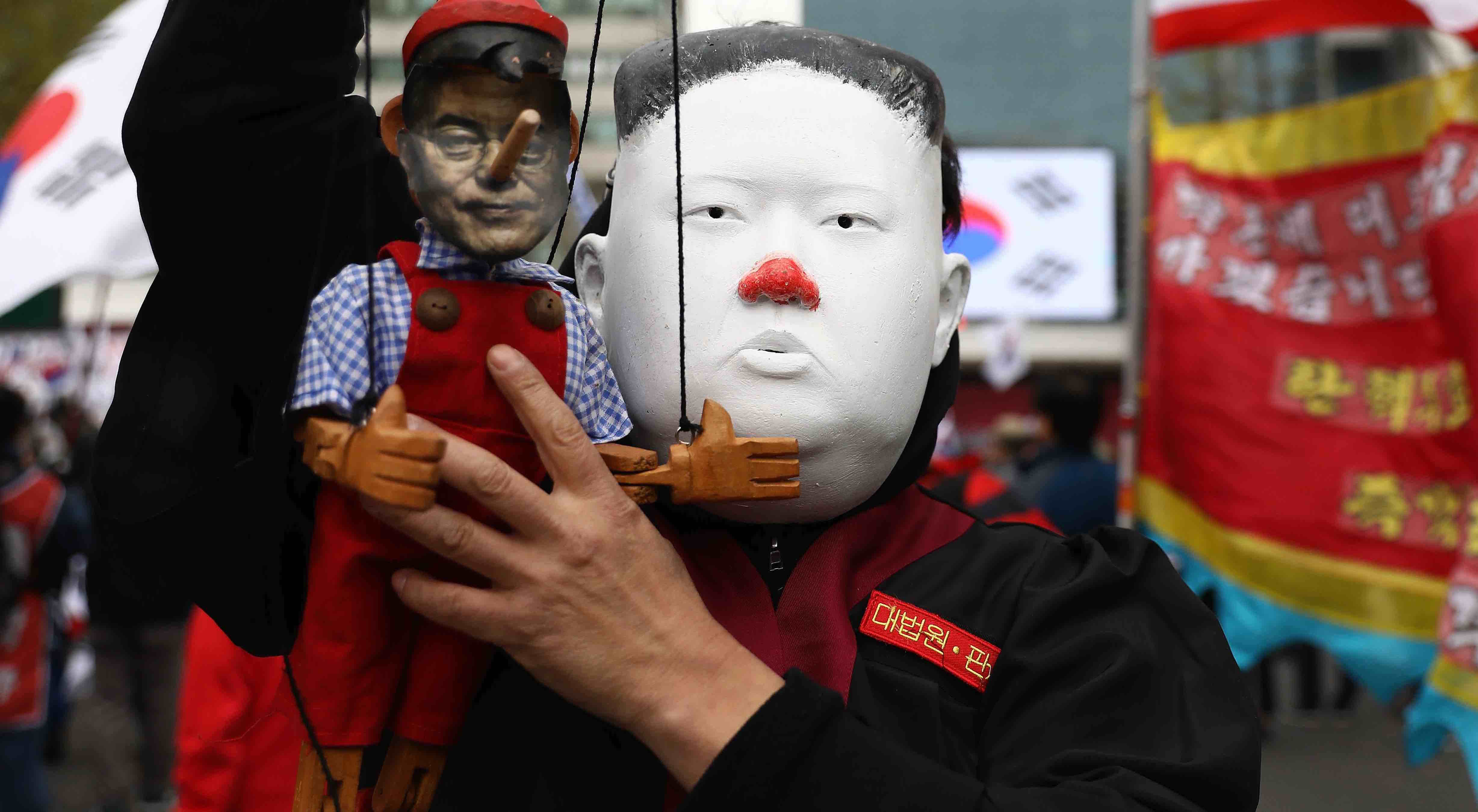 A protester in Seoul wearing a Kim Jong-un mask holds a doll of South Korea's Moon Jae-in (Photo: Chung Sung-Jun/Getty)