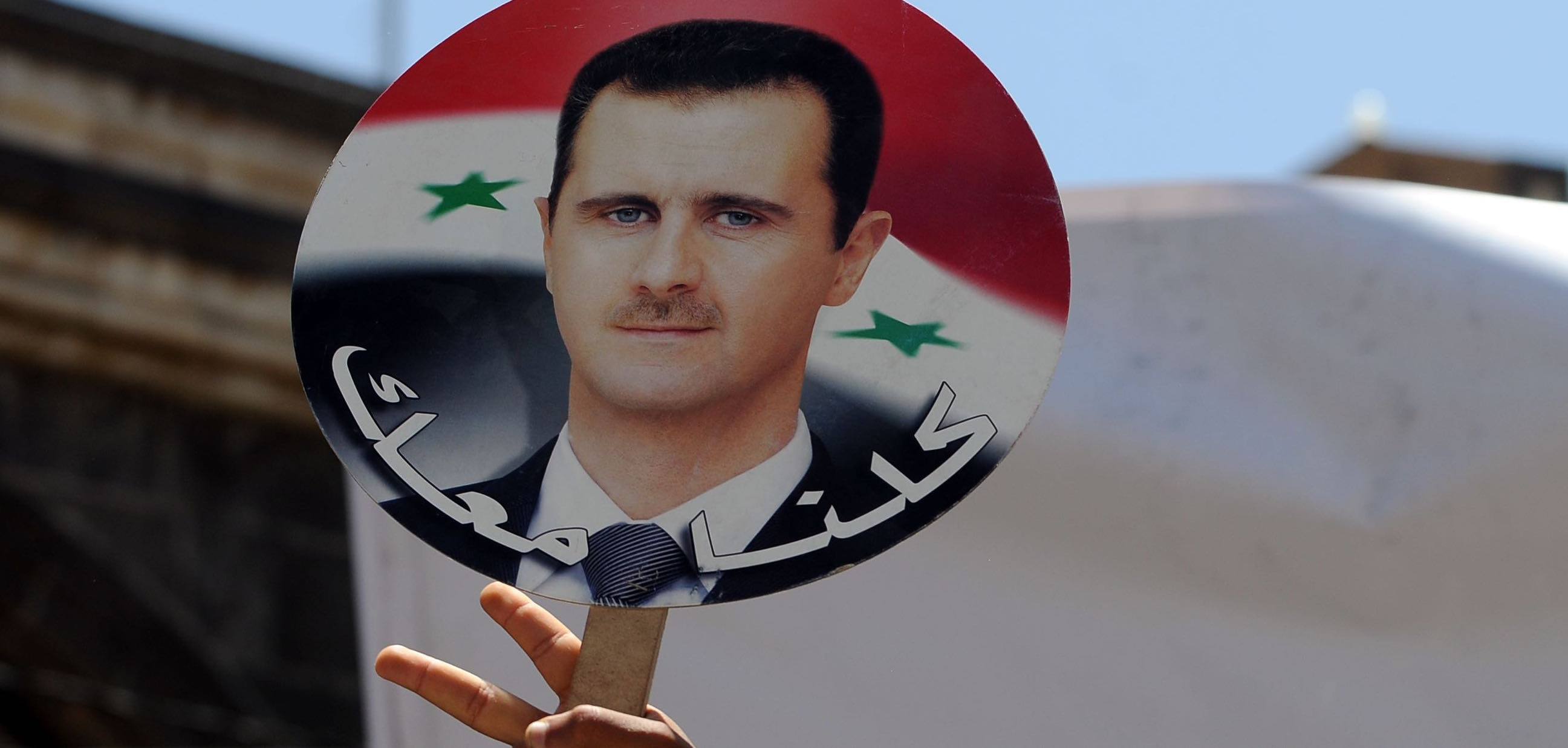 Yemeni protesters hold a photo of Syrian President Bashar al-Assad following US-led airstrikes (Photo: Mohammed Hamoud/Getty)