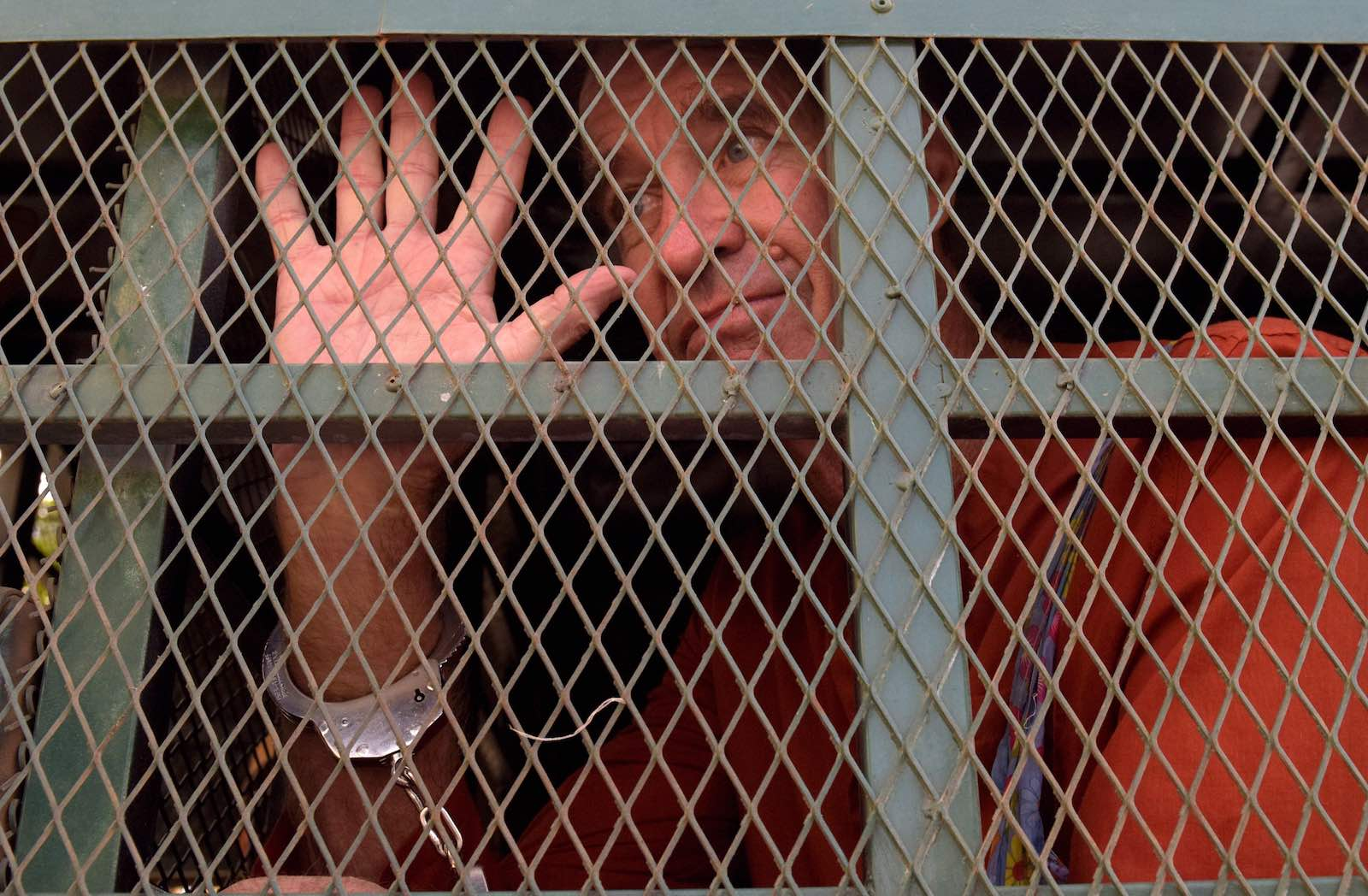Australian filmmaker James Ricketson arrives in a prison van for his trial at a Phnom Penh court in June (Photo: Tang Chhin Sothy via Getty)