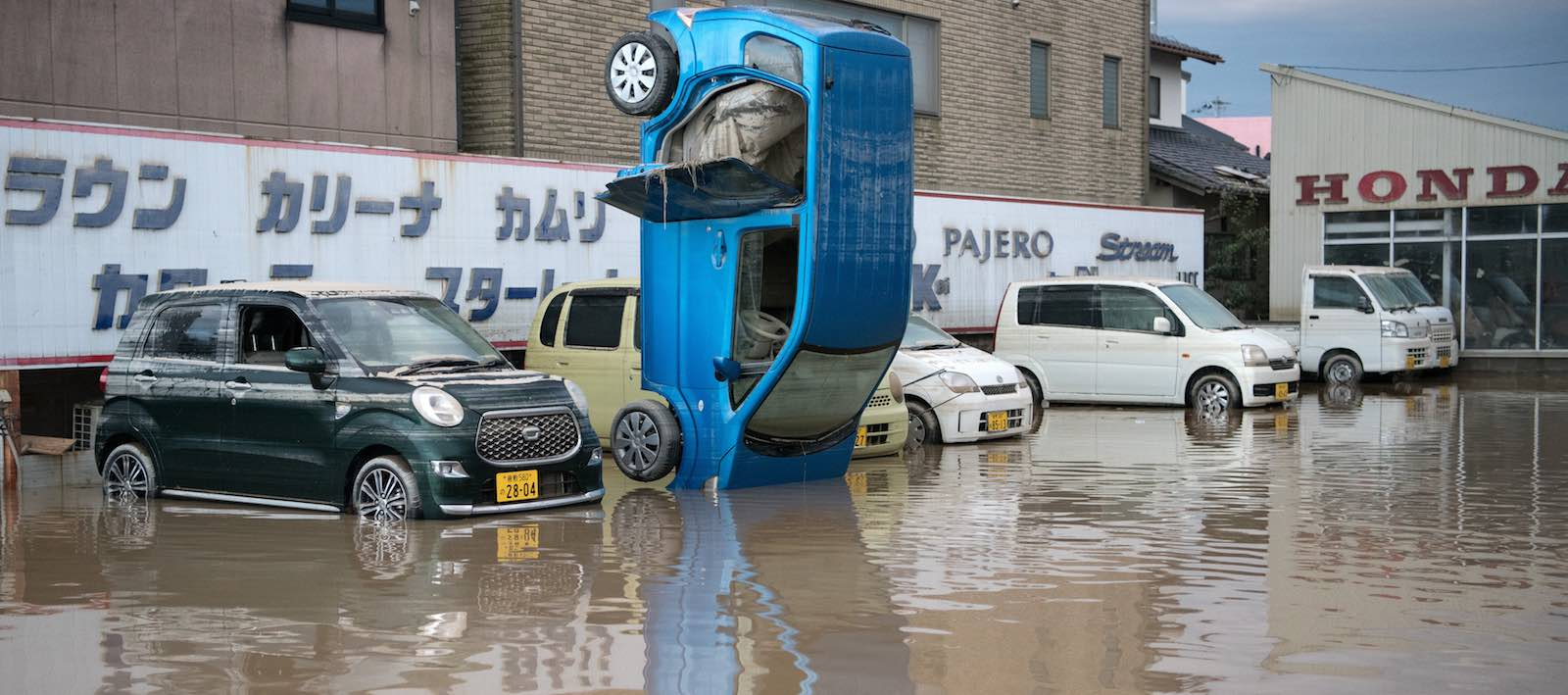 A car stands on its front following heavy flooding on 8 July in Kurashiki near Okayama, Japan (Photo: Carl Court/Getty)