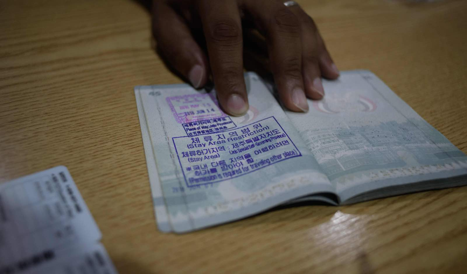 A Yemeni asylum seeker shows a South Korean visa in his passport in Jeju (Photo: Ed Jones via Getty)