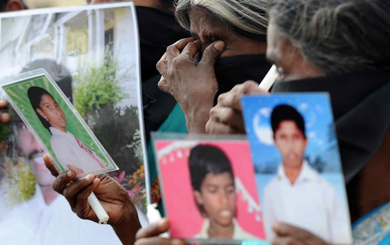 """Sri Lankan Tamil mothers from the """"Dead and Missing Person's Parents"""" group hold photographs in Jaffna, November 2013 (Photo: Lakruwan Wanniarachchi via Getty)"""