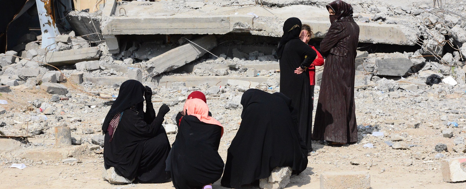 Women wait in front of building debris as Iraqi civilians head for shelter in Mosul on 26 March. (Photo by Hamit Huseyin/Getty Images)
