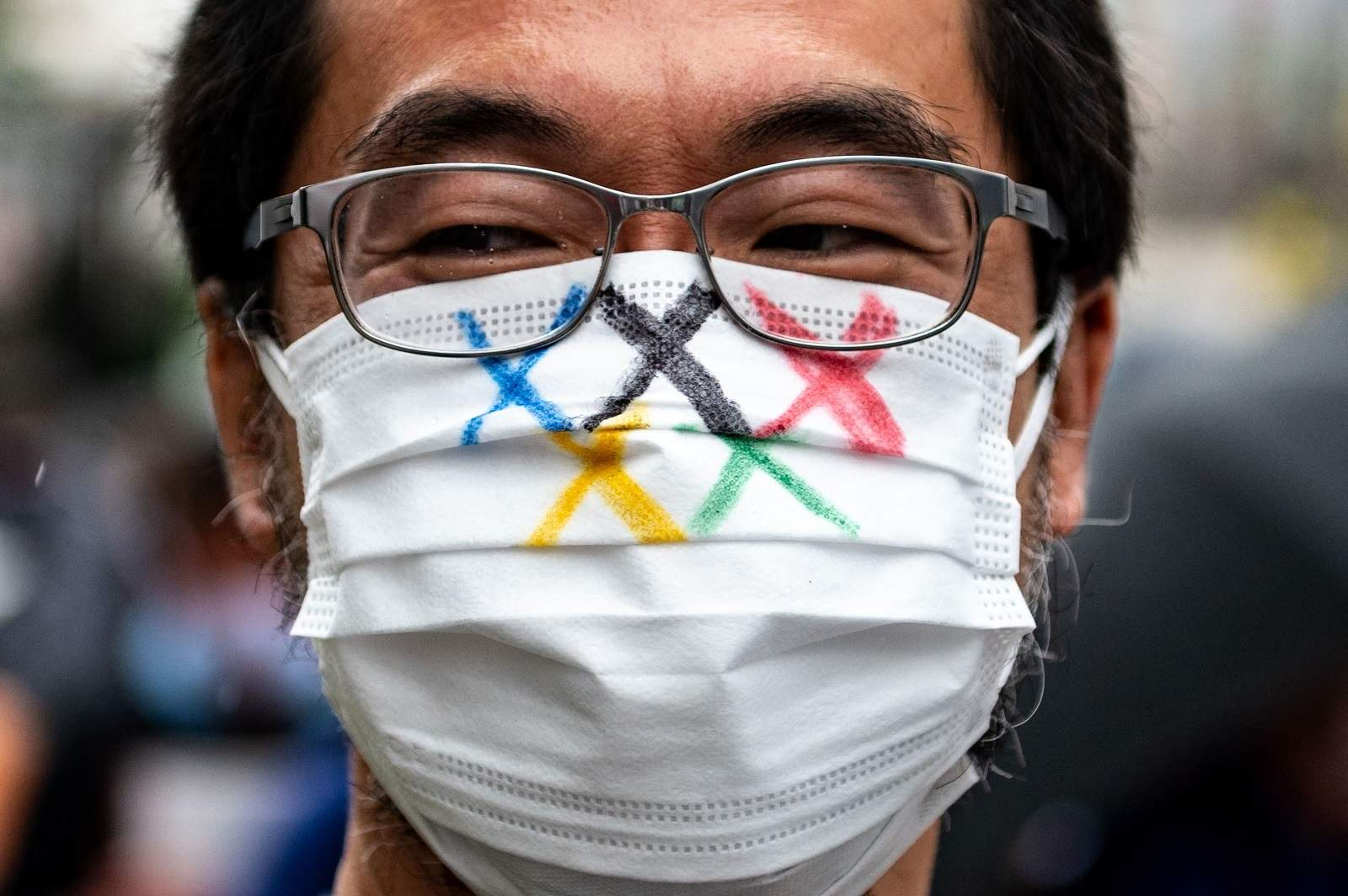 An activist marches to Tokyo's Metropolitan Government Building to protest against the Tokyo Olympics, 19 June 2021 (Philip Fong/AFP via Getty Images)