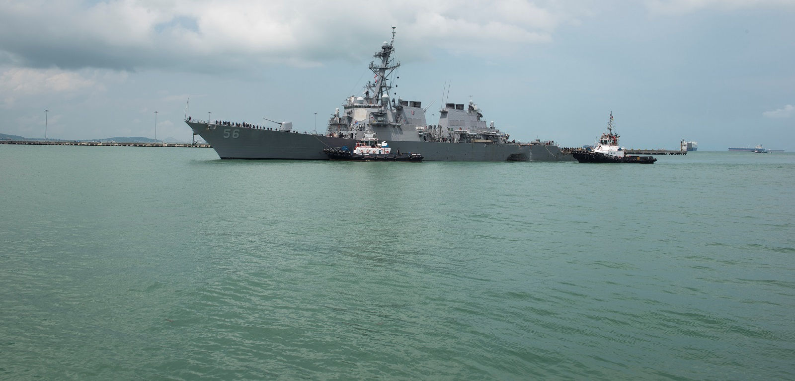 Tugboats assist the USS John S. McCain as it steers towards Changi Naval Base following the 21 August collision with a merchant vessel. (Photo: US Navy via Getty Images)