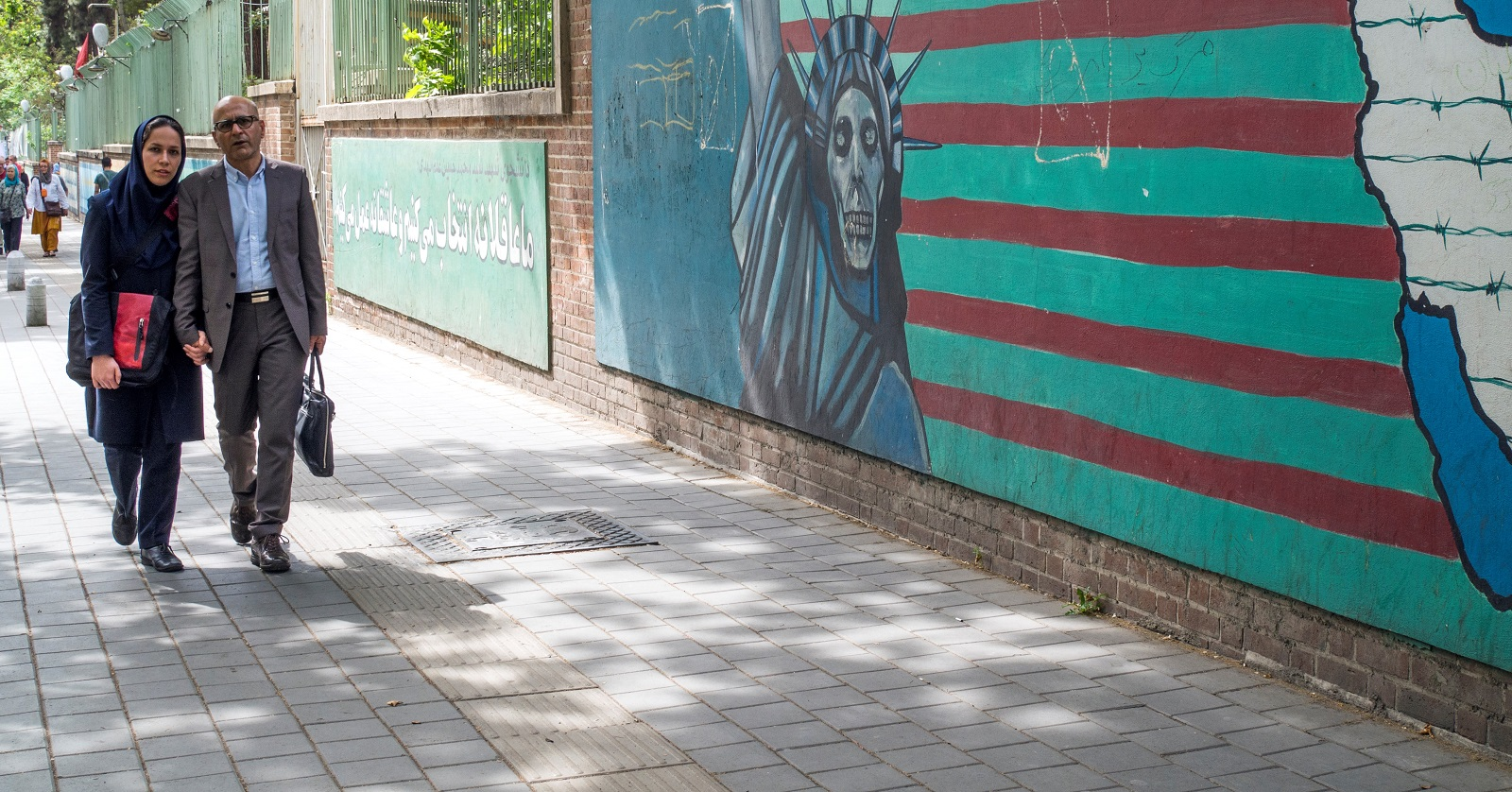 Pedestrians walk past a painting of the Statue of Liberty as a skeleton outside the former American embassy in Tehran. (Photo by Leisa Tyler/Getty Images)