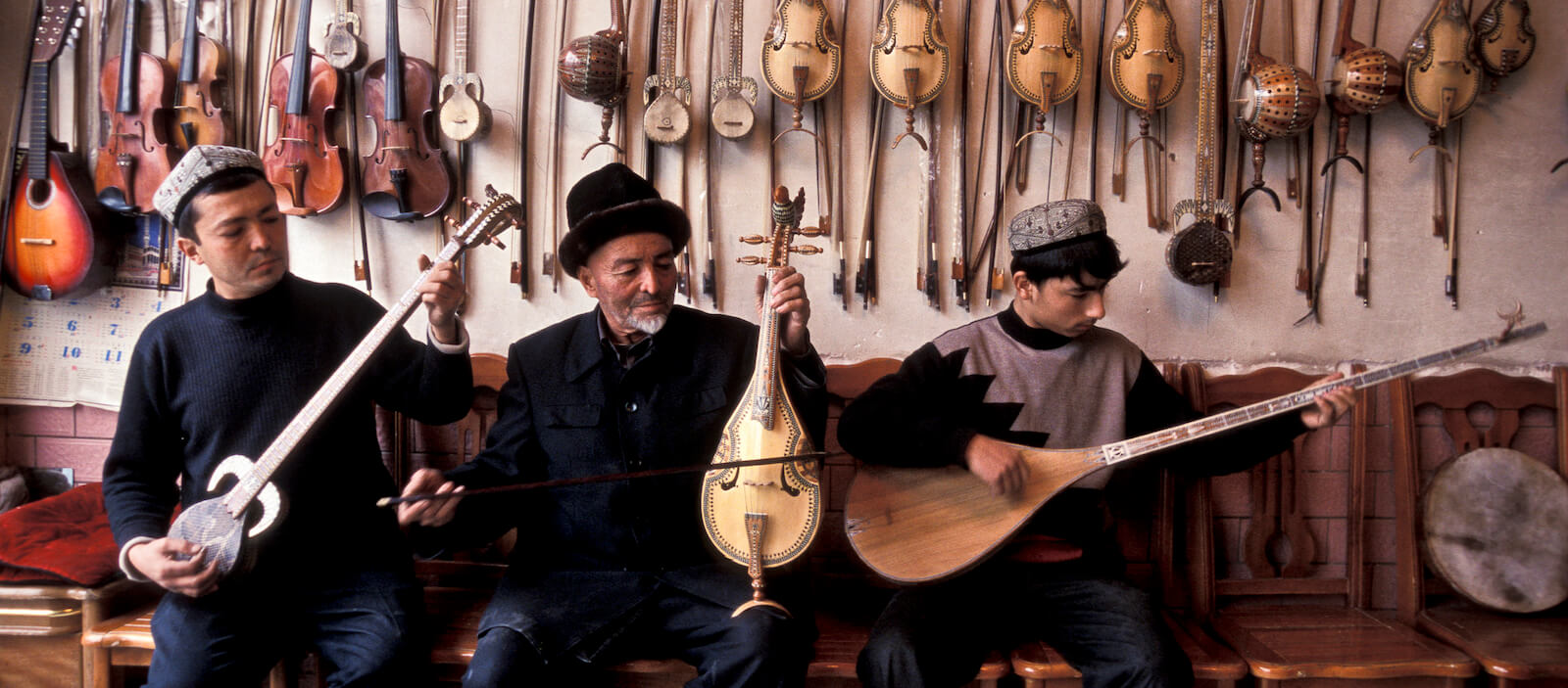 Ababekry Selay with son and employee playing traditional Uighur music in their shop in Kashgar city (Photo: Christopher Pillitz/Getty)