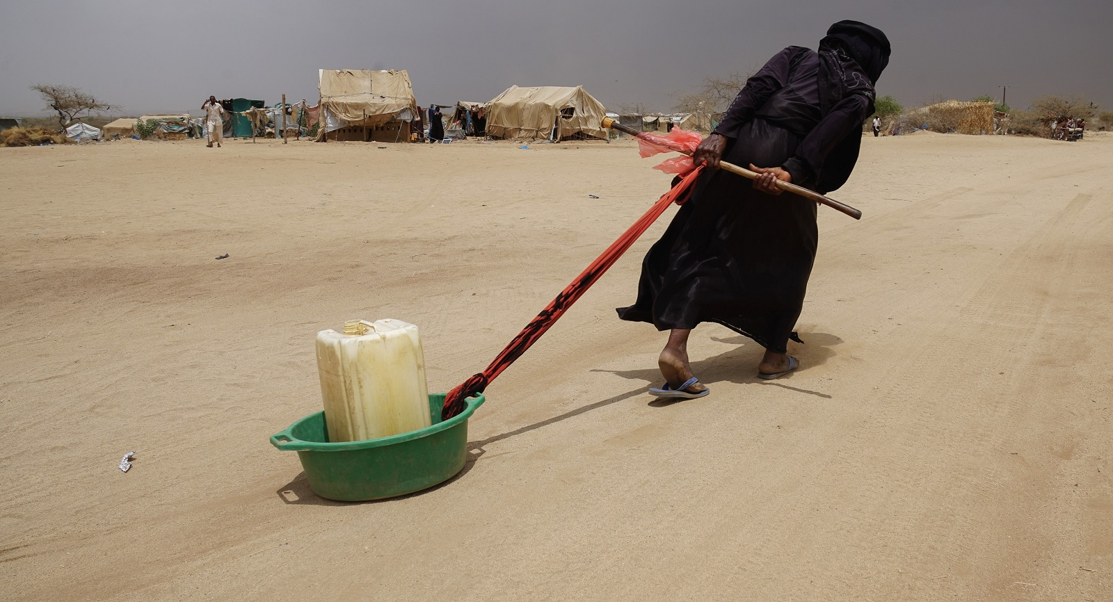 A displaced Yemeni woman drags water back to her tent in an ABS IDP camp. (Photo: Giles Clarke, UN OCHA/Getty Images)