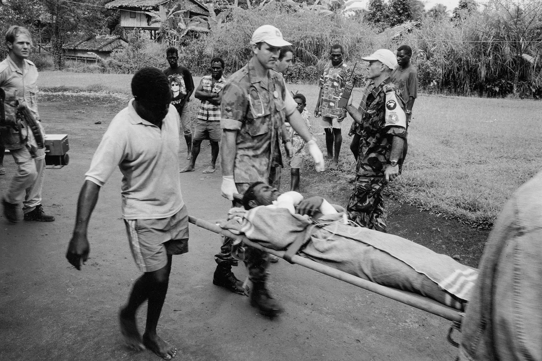 Peace Monitoring Group troops from Australia and New Zealand help medevac an injured man in Bana district, Bougainville, 2000