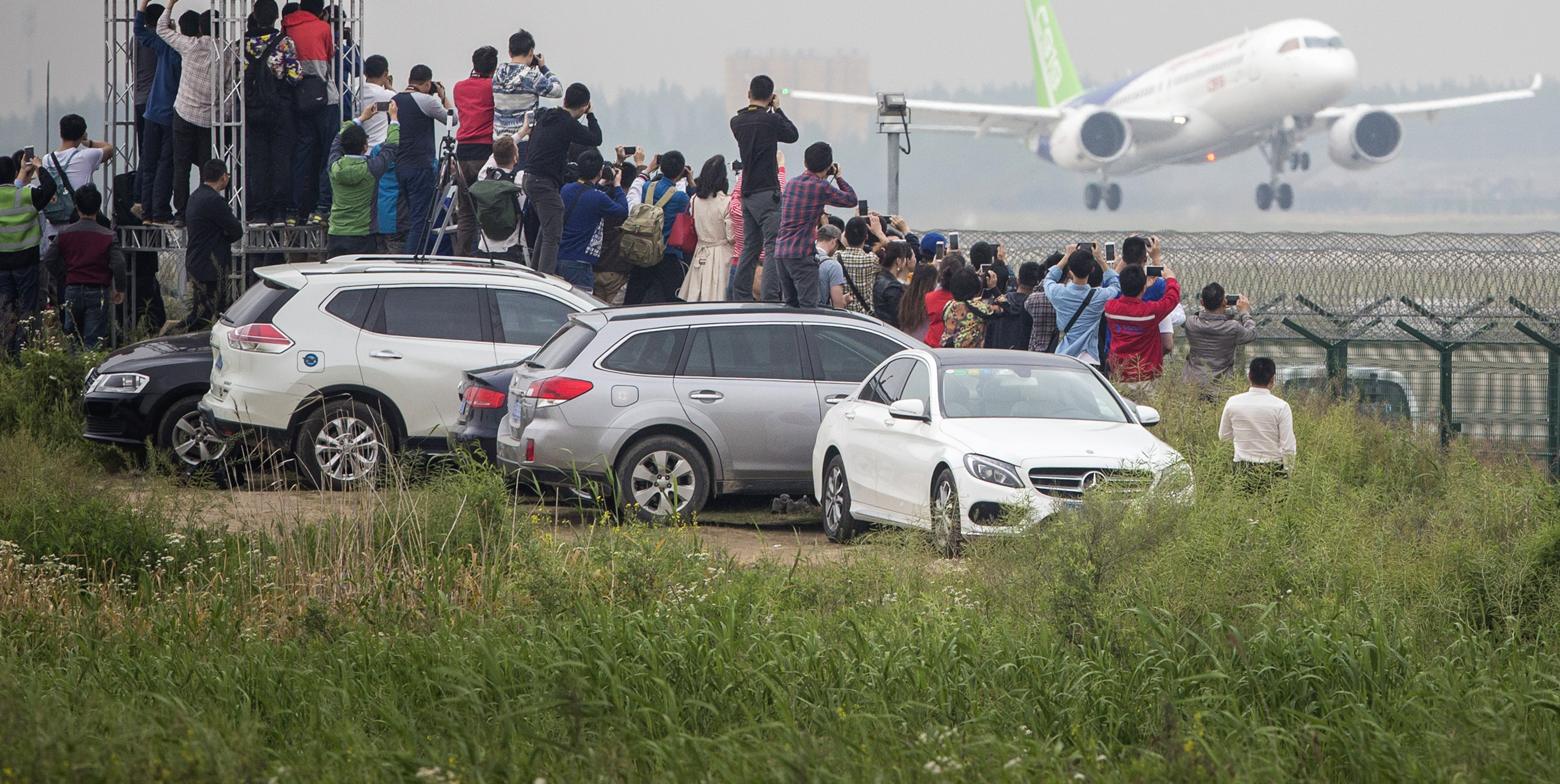Enthusiasts watch the COMAC C919's maiden flight, 5 May 2017. (Getty/Bloomberg)