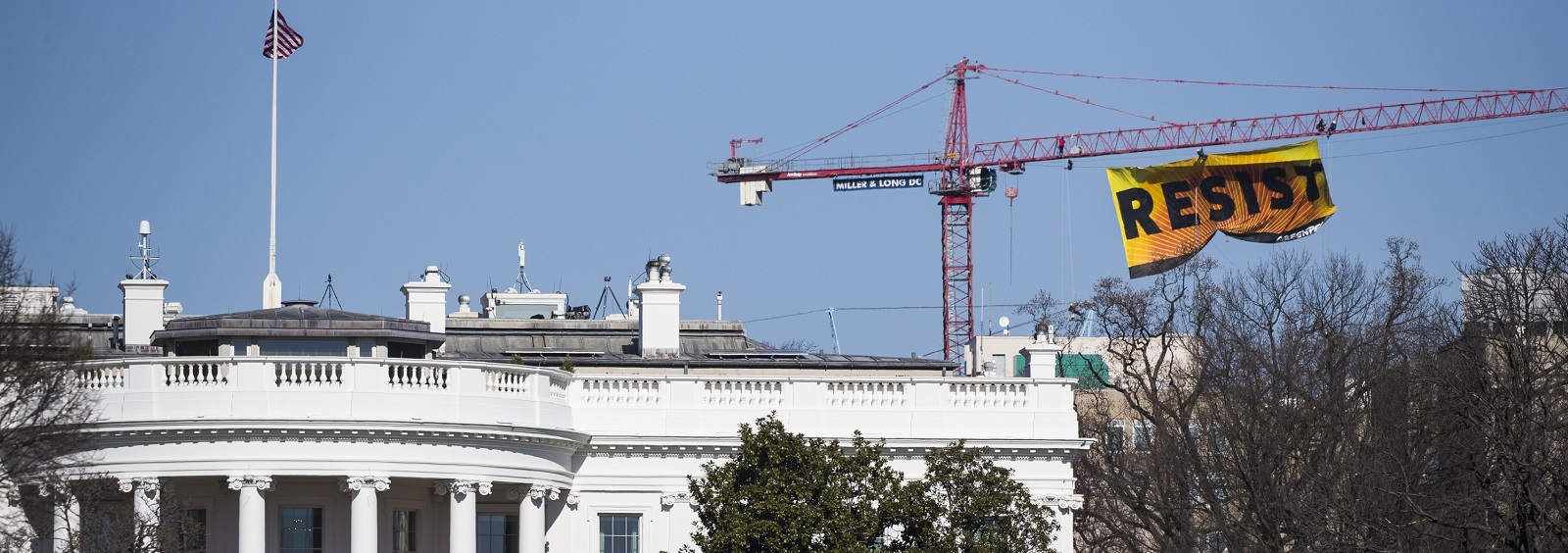 An anti-Trump sign saying 'resist' hung from a crane by Greenpeace seen behind the White House. (Photo by Samuel Corum/Anadolu Agency/Getty Images)