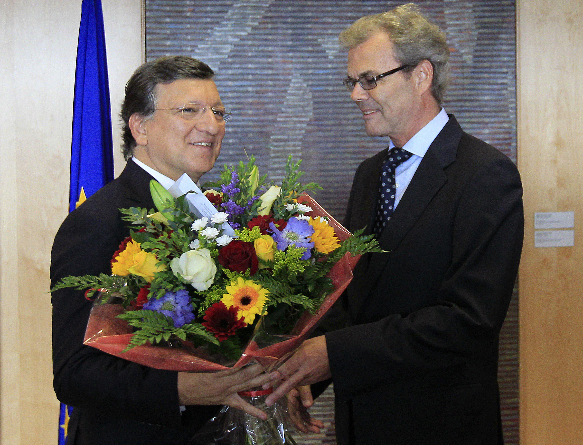 European Commission President Jose Manuel Barroso (left) receives flowers from Atle Leikvoll, Norway's Ambassador to the European Union.