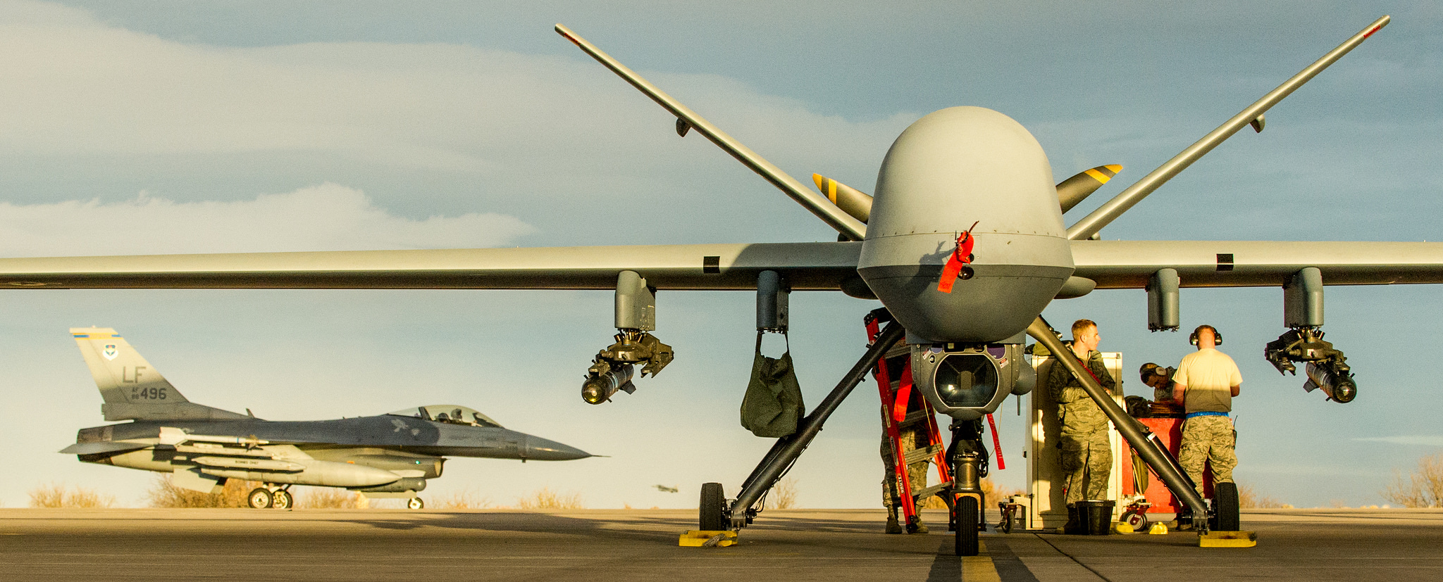 An MQ-9 Reaper with an F-16 in the background. (Airman Magazine/ Flickr)