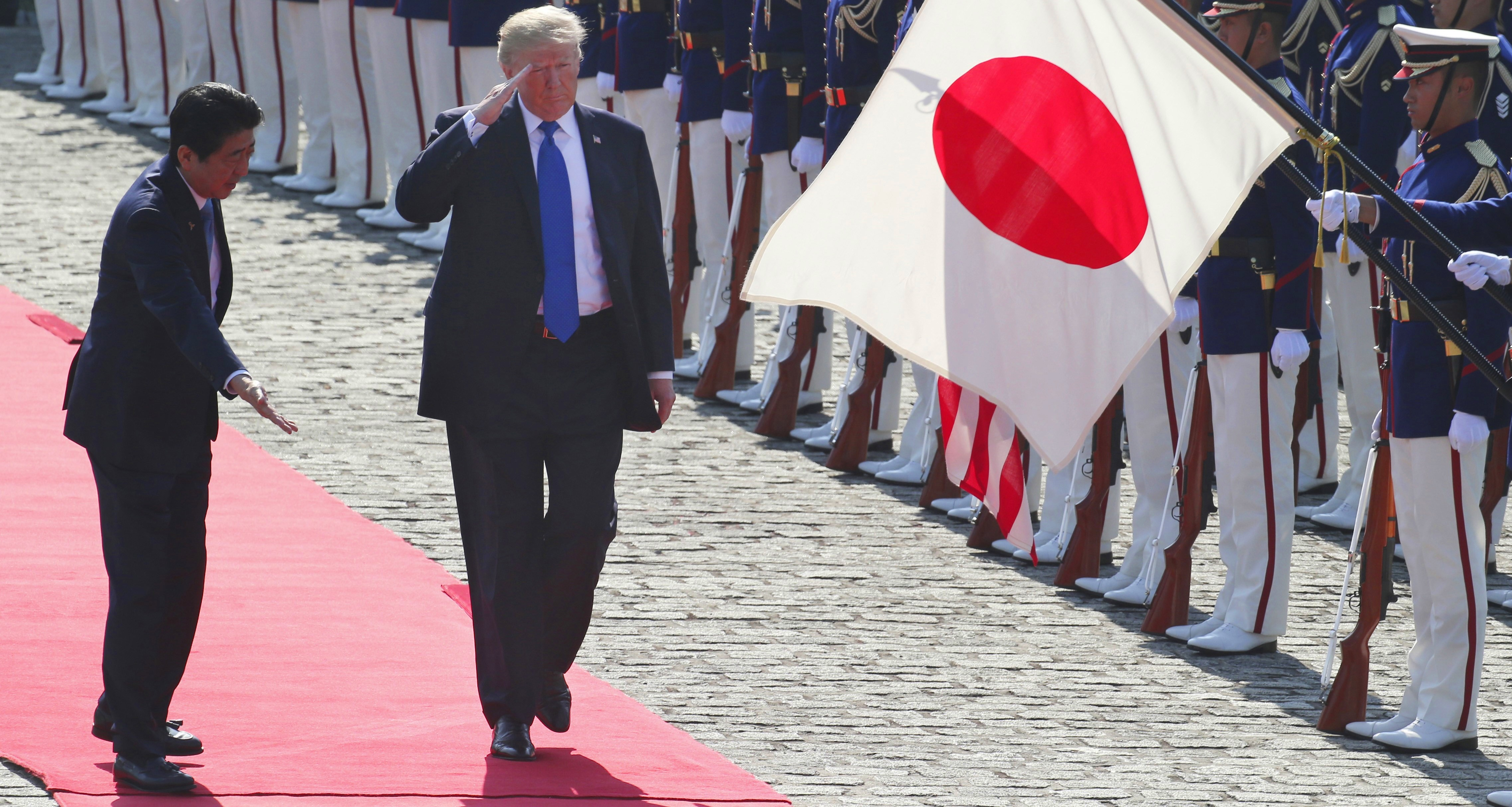 President Donald Trump and Prime Minister Shinzo Abe walk past honour guards at Akasaka Palace in Tokyo on 6 November. (Photo by Koji Sasahara/Getty)